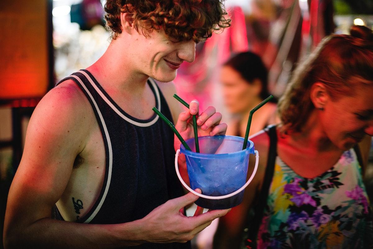 A tourist enjoying bucket drink in Khao San Road , Bangkok, Thailand