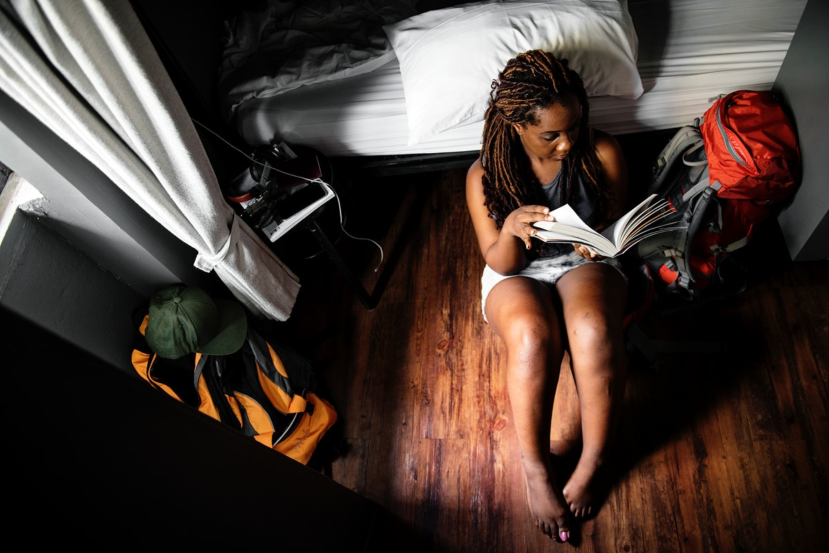 An African descent woman sitting on the wooden floor reading a book