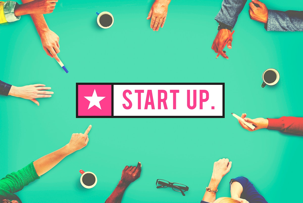 Aerial view of diverse hands pointing to startup word