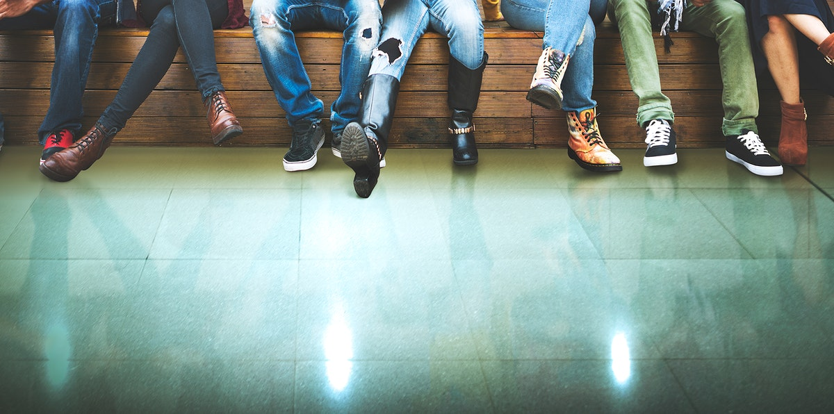 Closeup group of people legs sitting together with green floor