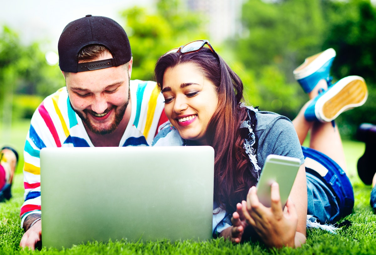 Couple lying down on the grass using laptop