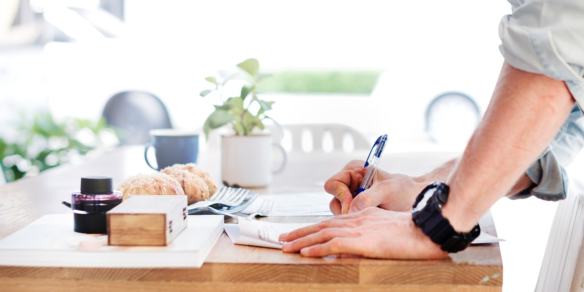 Side view of hand writing on paper on wooden table with bakery