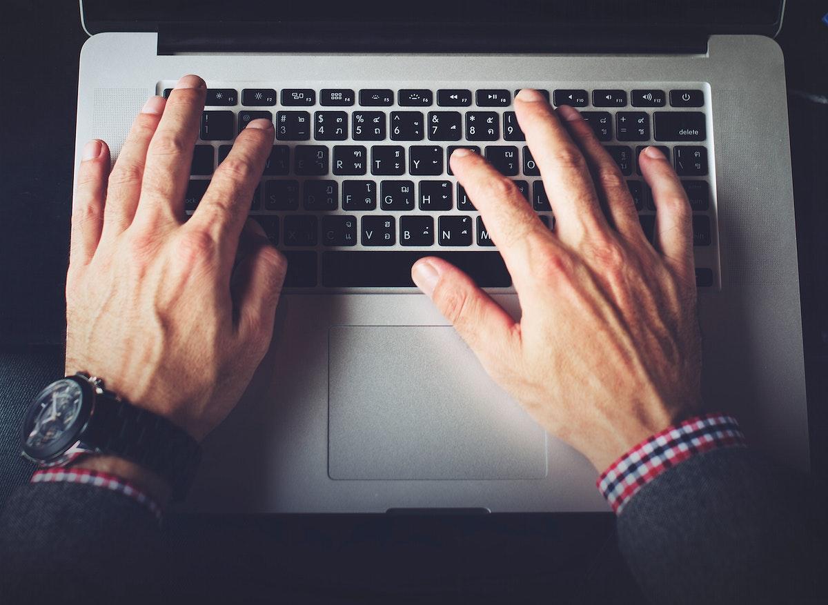 Closeup of hands using laptop keyboard
