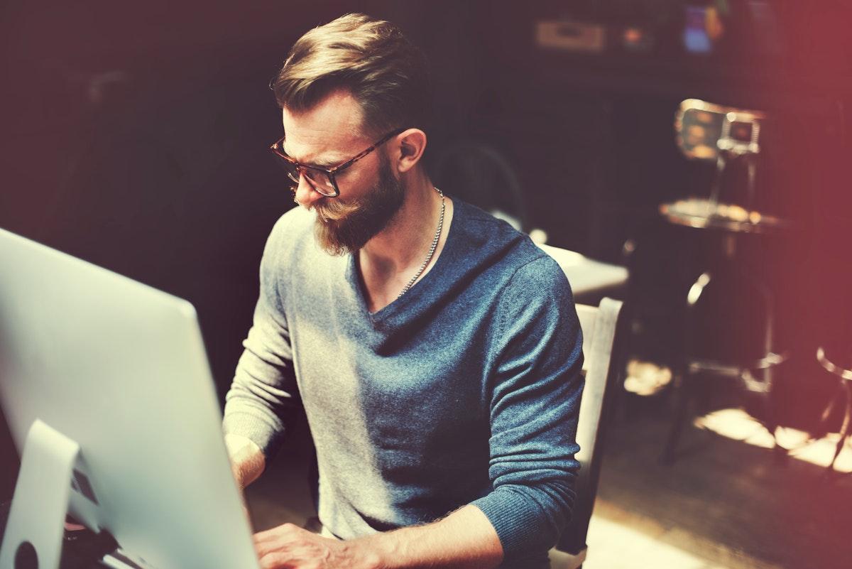 Caucasian man sitting working on computer pc