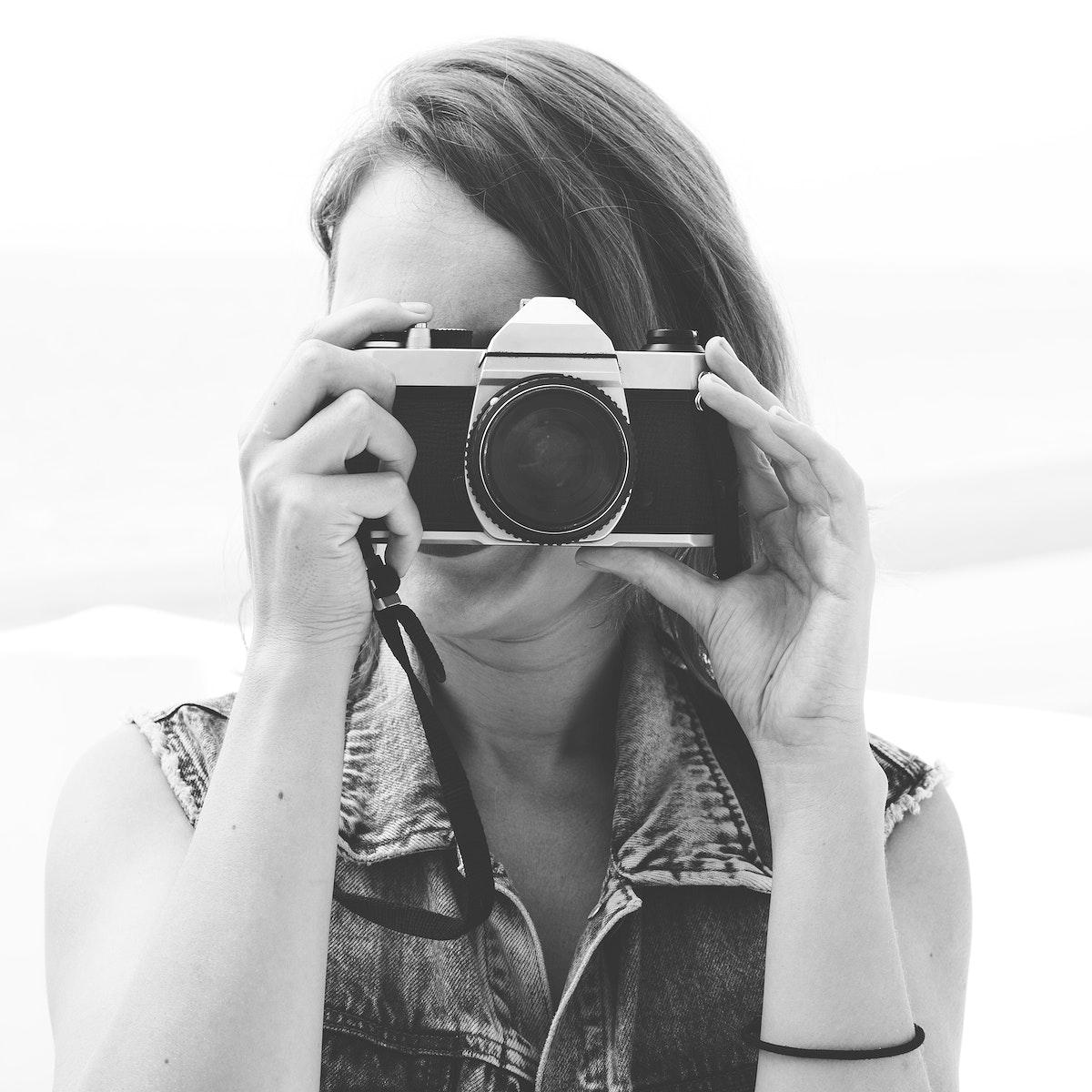Closeup of woman using camera taking photo grayscale