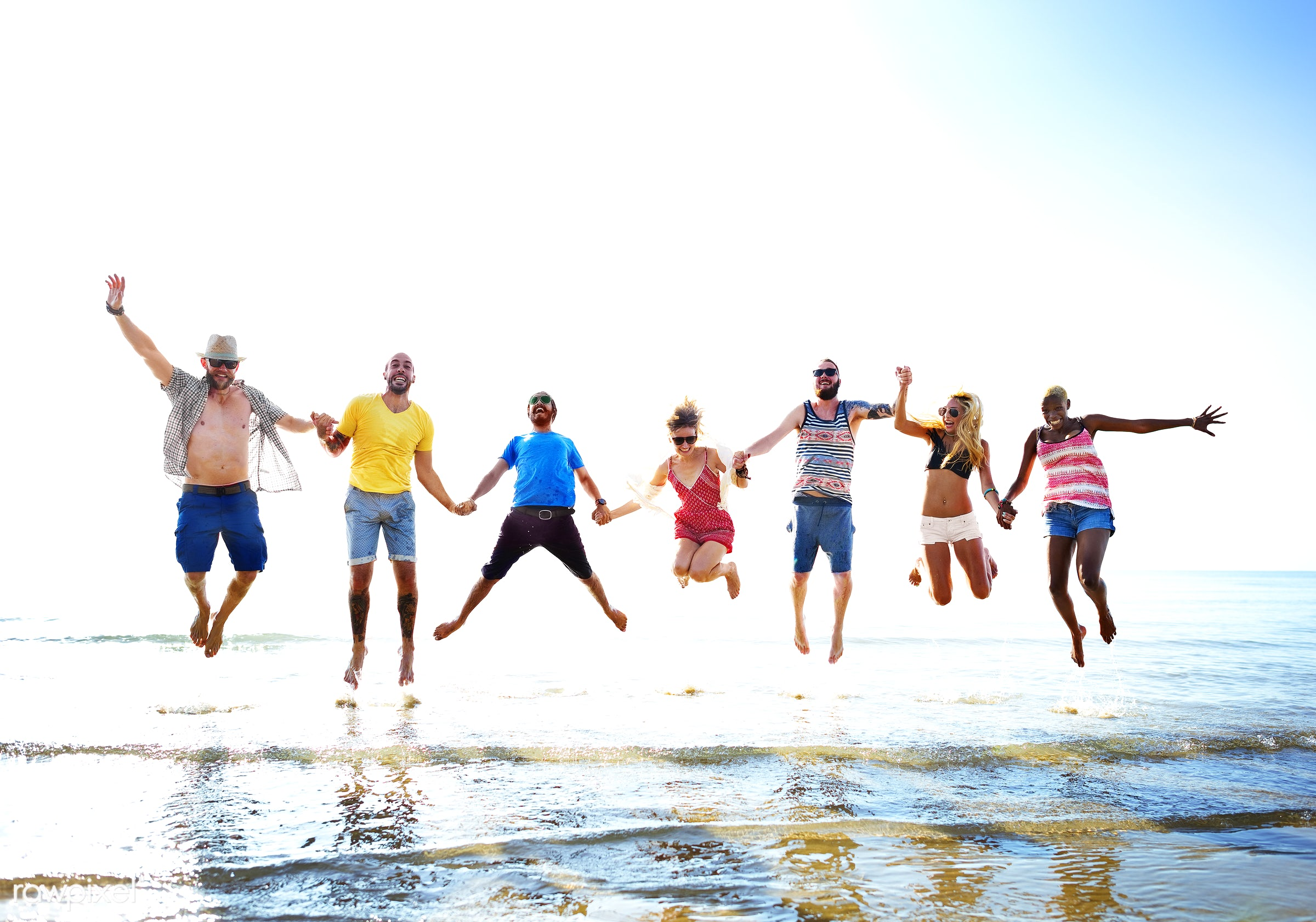 Friends playing in the water at the beach - happiness, fun, lifestyle, sea, beach, jump, diverse, excited, action, african...