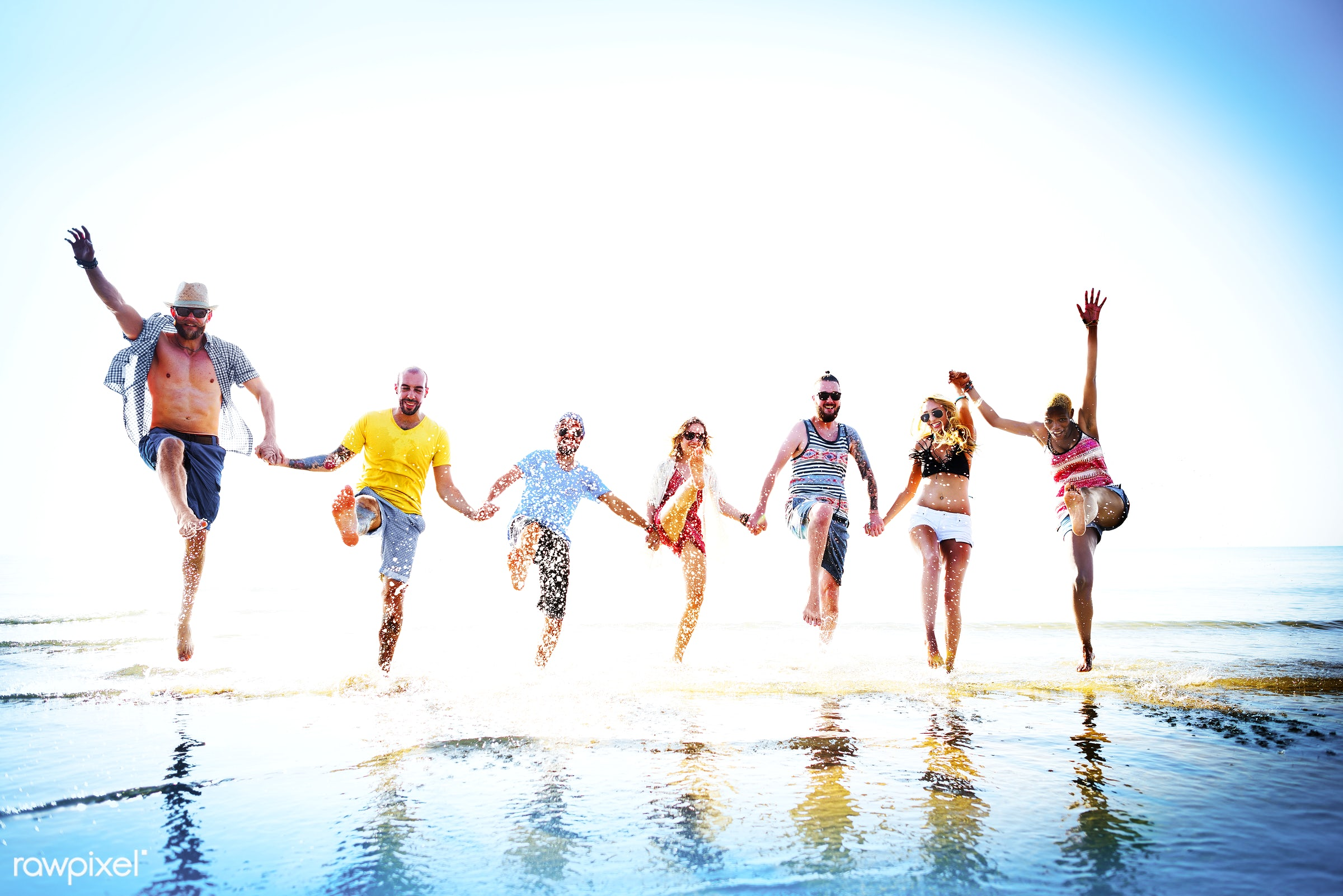 Friends playing in the water at the beach - action, african descent, asian ethnicity, beach, bonding, cheerful, chilling,...