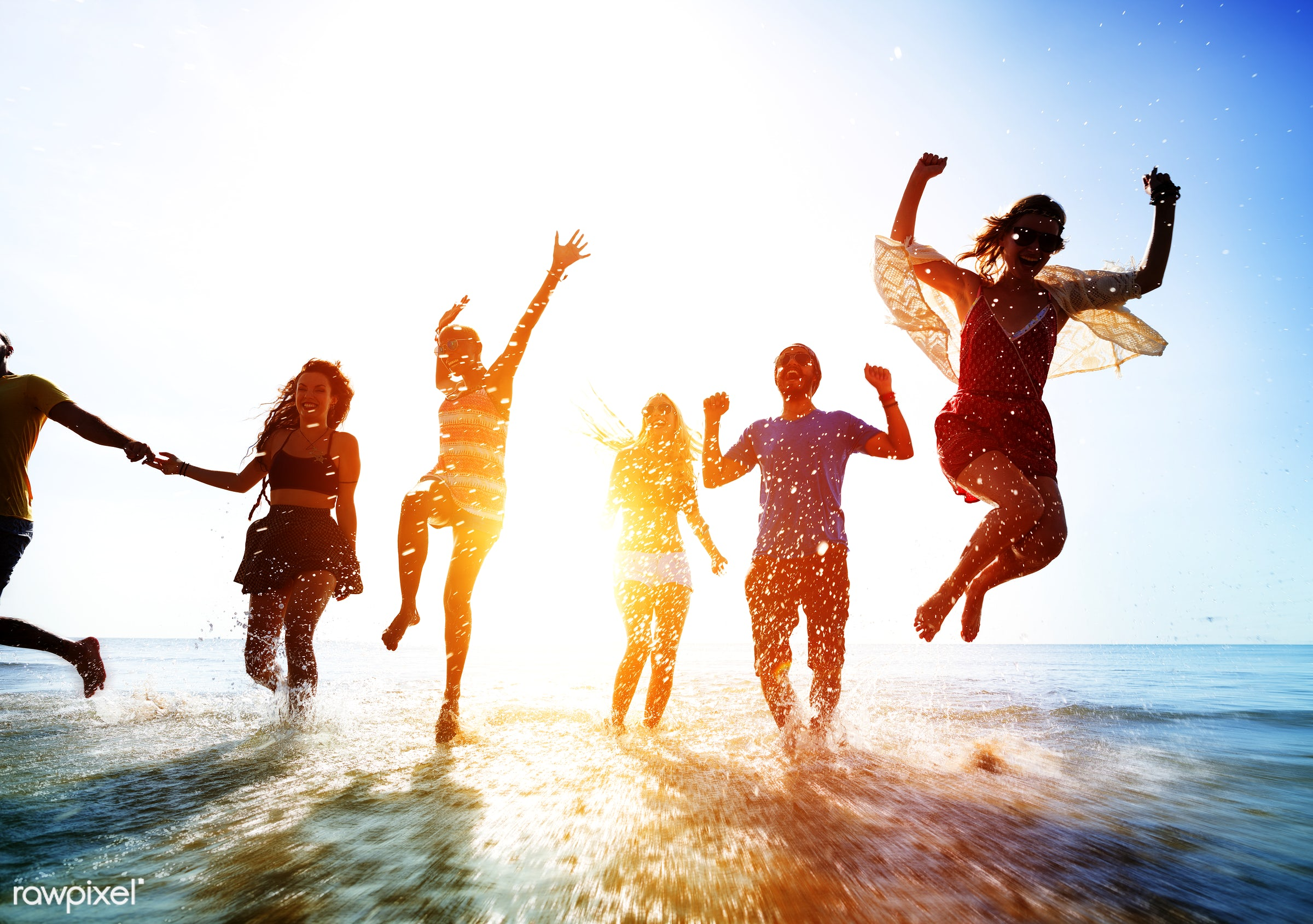 Friends playing in the water at the beach - running, water, sun, energy, action, african descent, arms raised, backlit,...