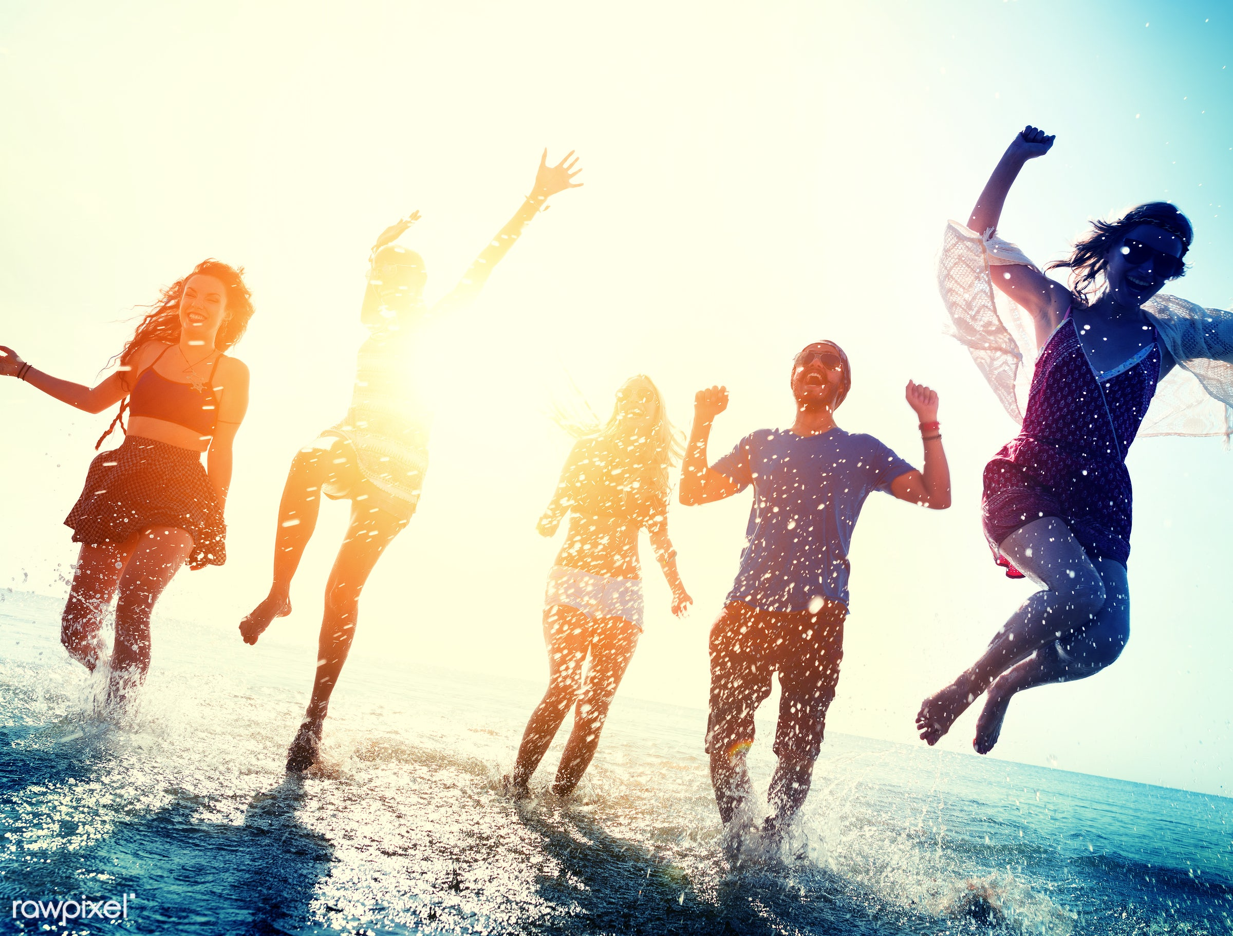 Friends playing in the water at a beach - running, beach, fun, action, african descent, arms raised, backlit, blurred,...