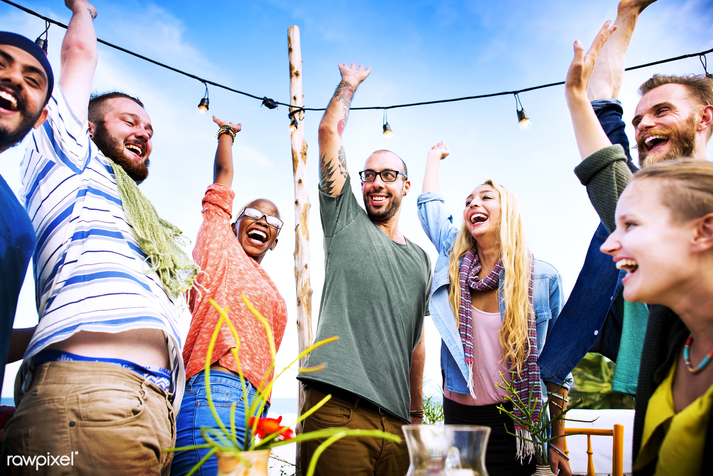 Rooftop party by the beach - arms raised, balcony, beach, bonding, casual, celebration, cheerful, diverse, diversity, event...