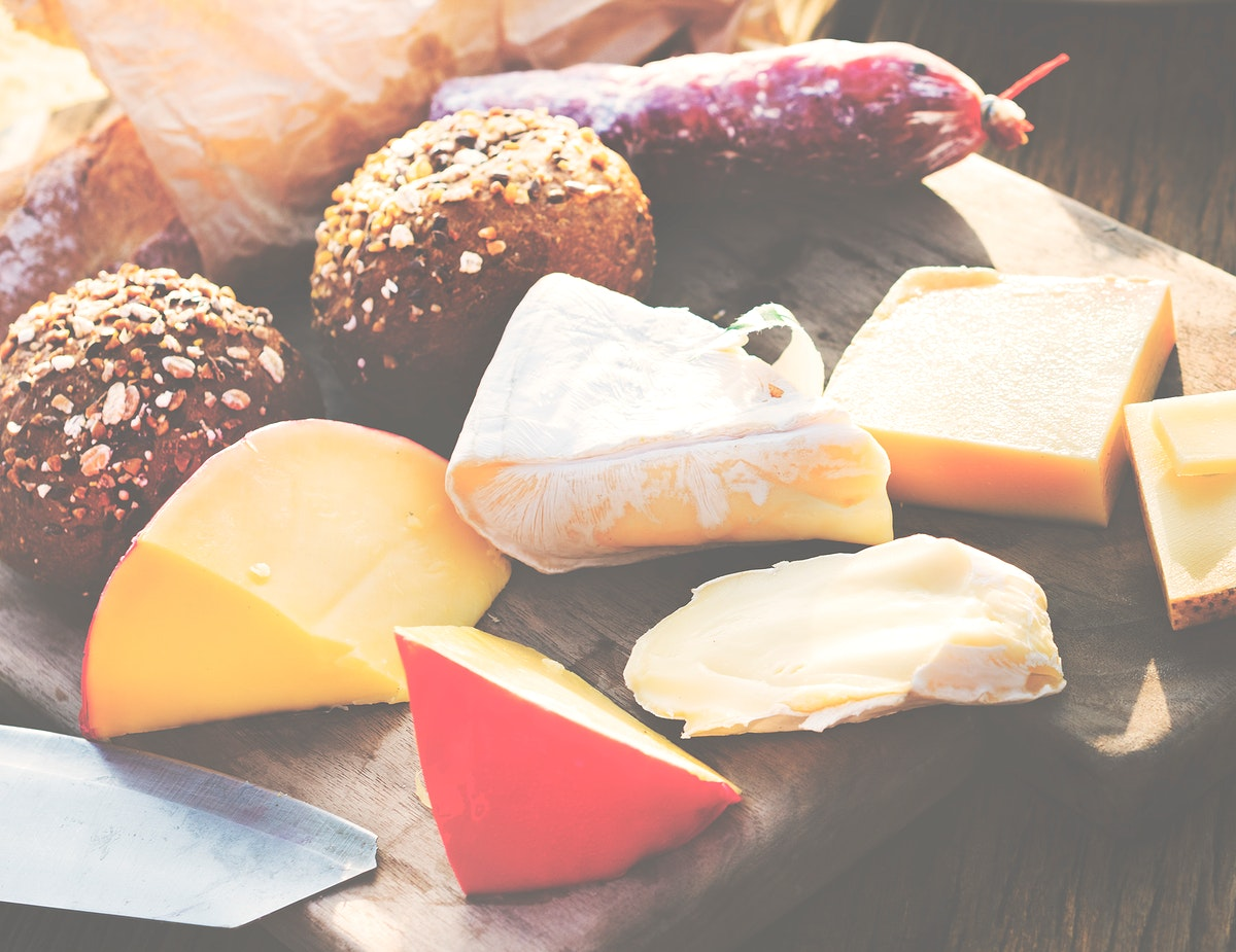 Closeup of various cheeses on wooden table with buns