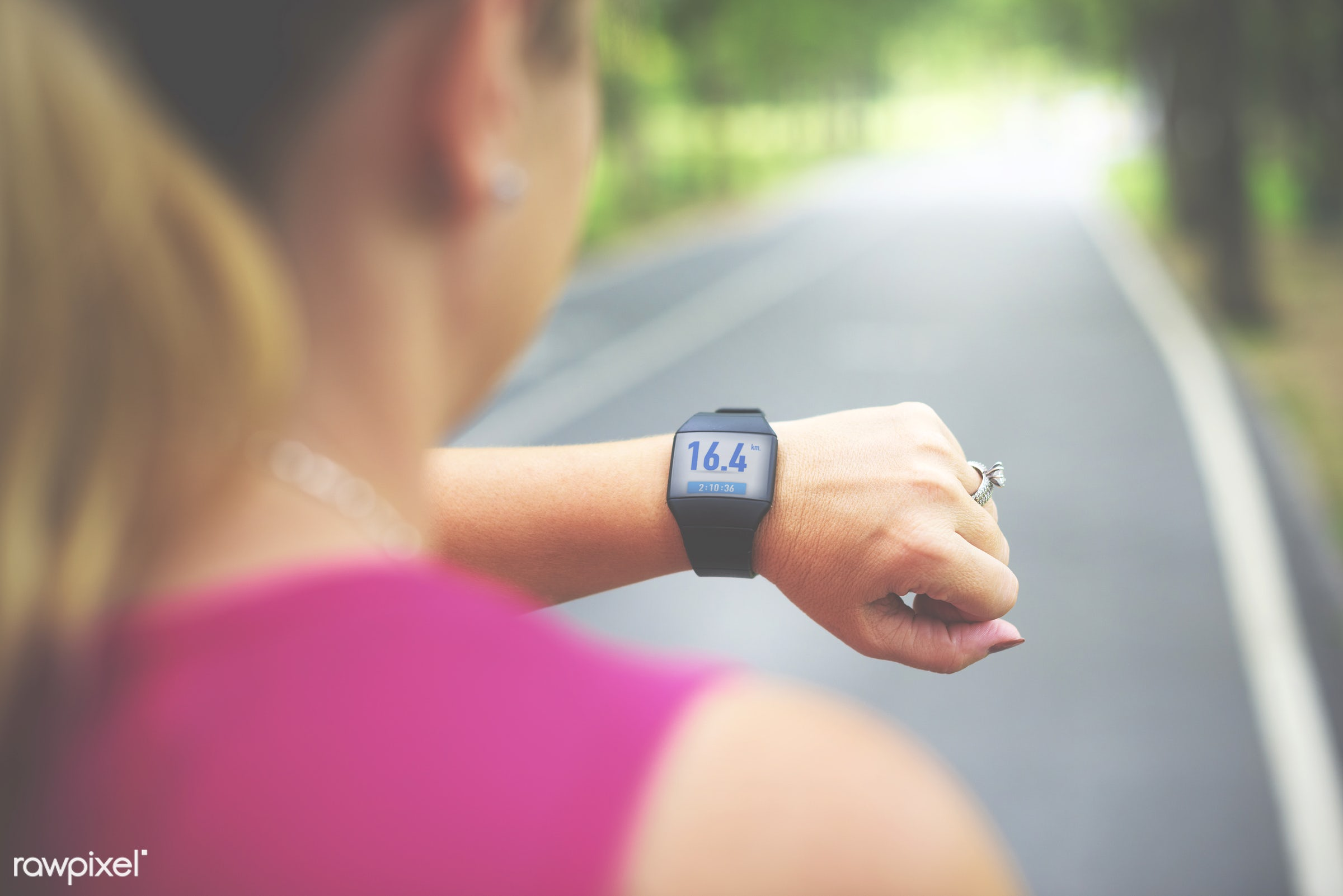 Woman checking distance on smartwatch - wellness, fitness, app, smartwatch, runner, practice, media, healthy, active,...