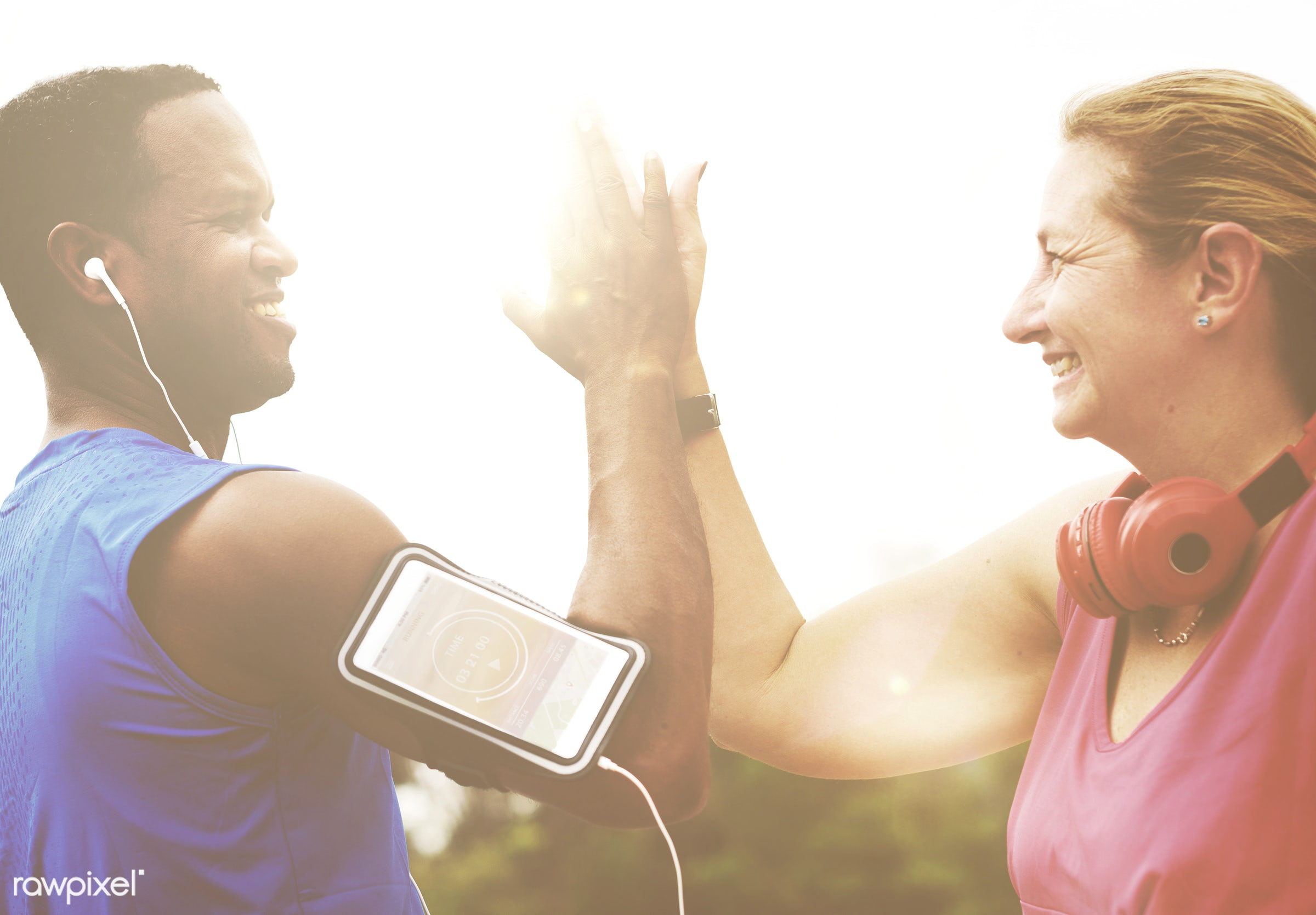 Couple doing a high five while working out - active, activity, adult, african american, caucasian, couple, device, diversity...