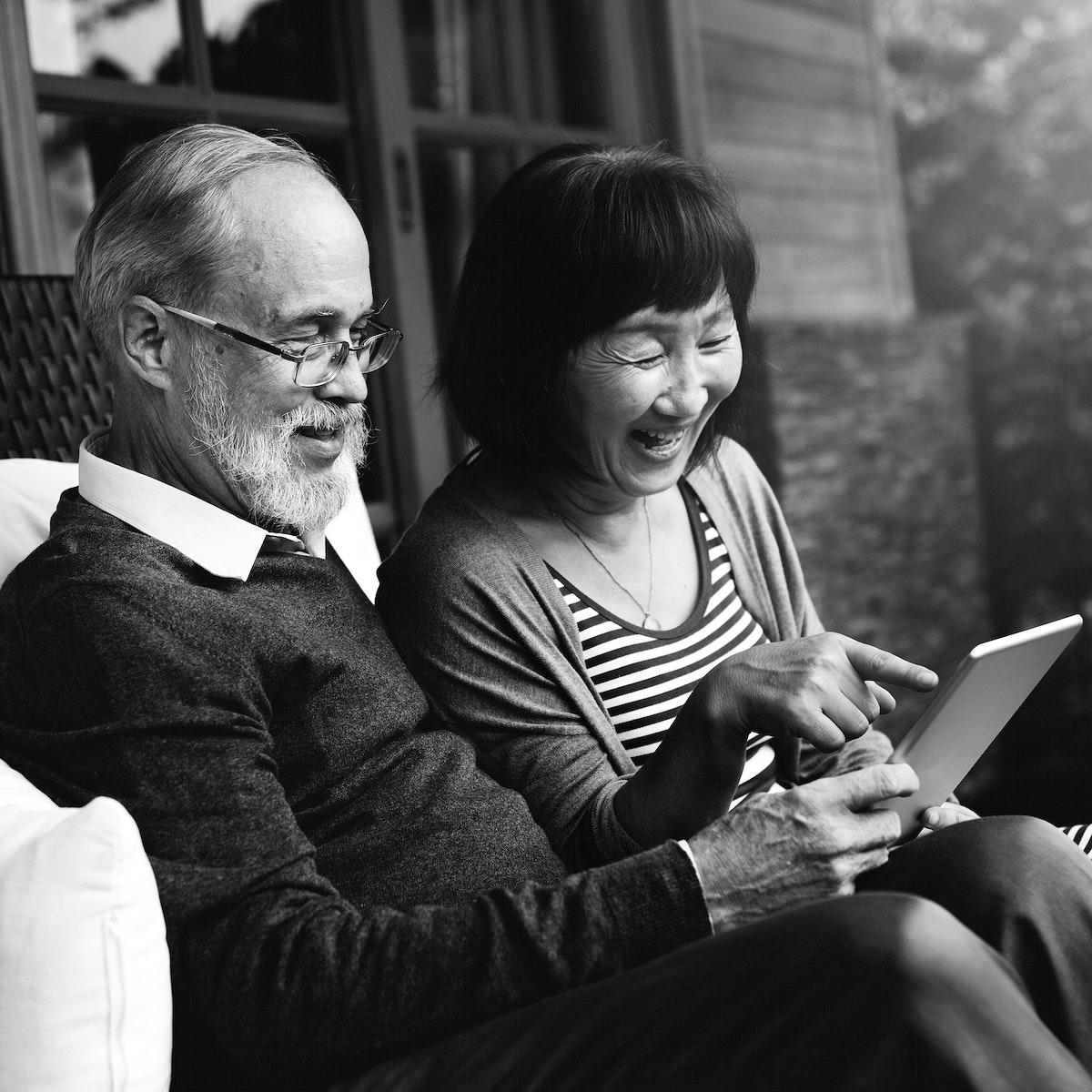 Senior couple sitting using tablet together