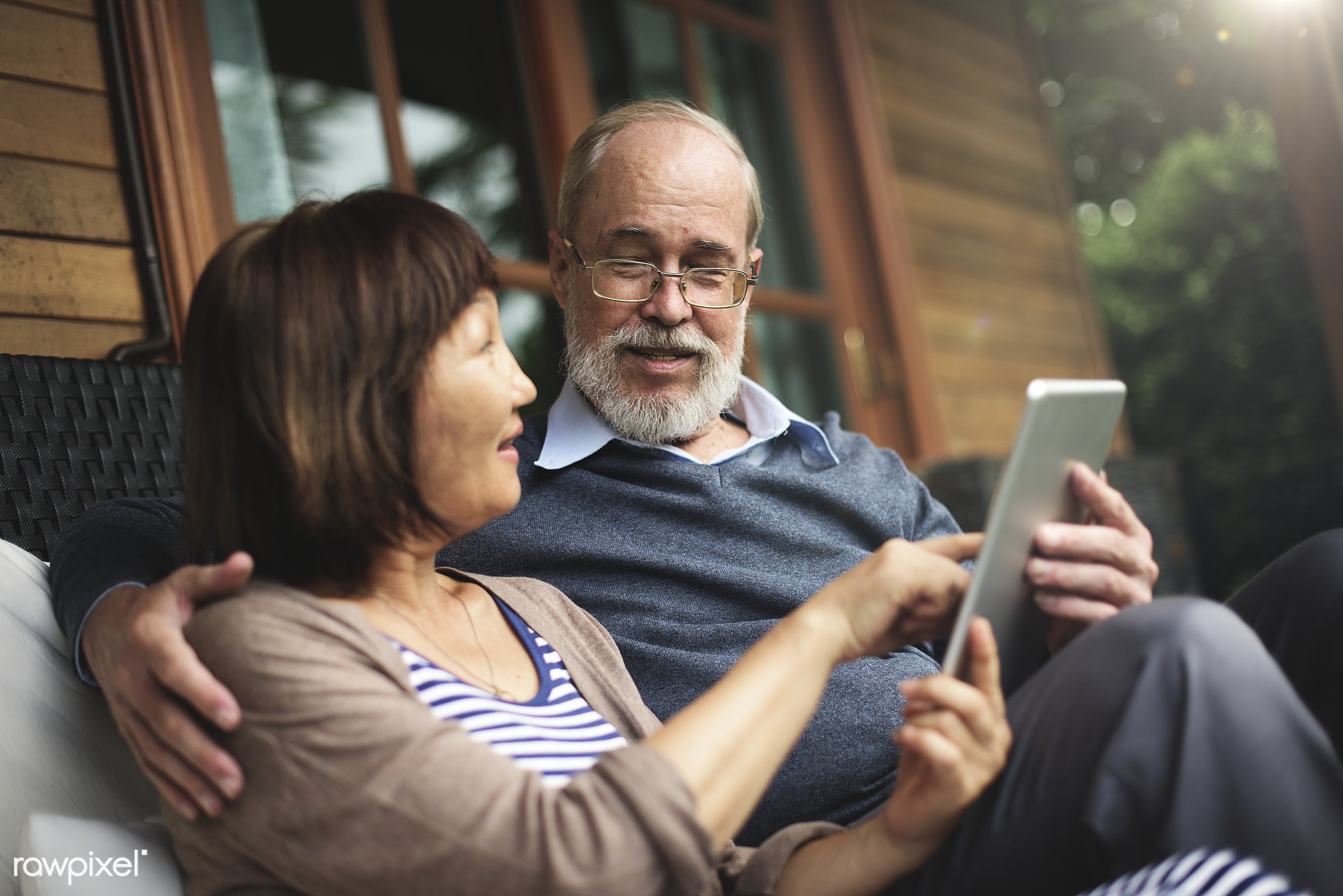 Senior couple using a tablet together - retirement, autumn, door, couple, adult, asian, asian ethnicity, bonding, chair,...