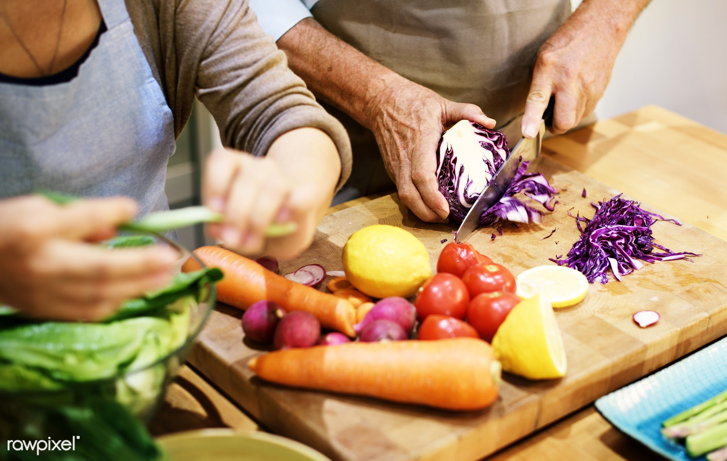 Senior couple cooking together in the kitchen - cooking, chopping, activity, adult, apron, breakfast, care, casual, cheerful...
