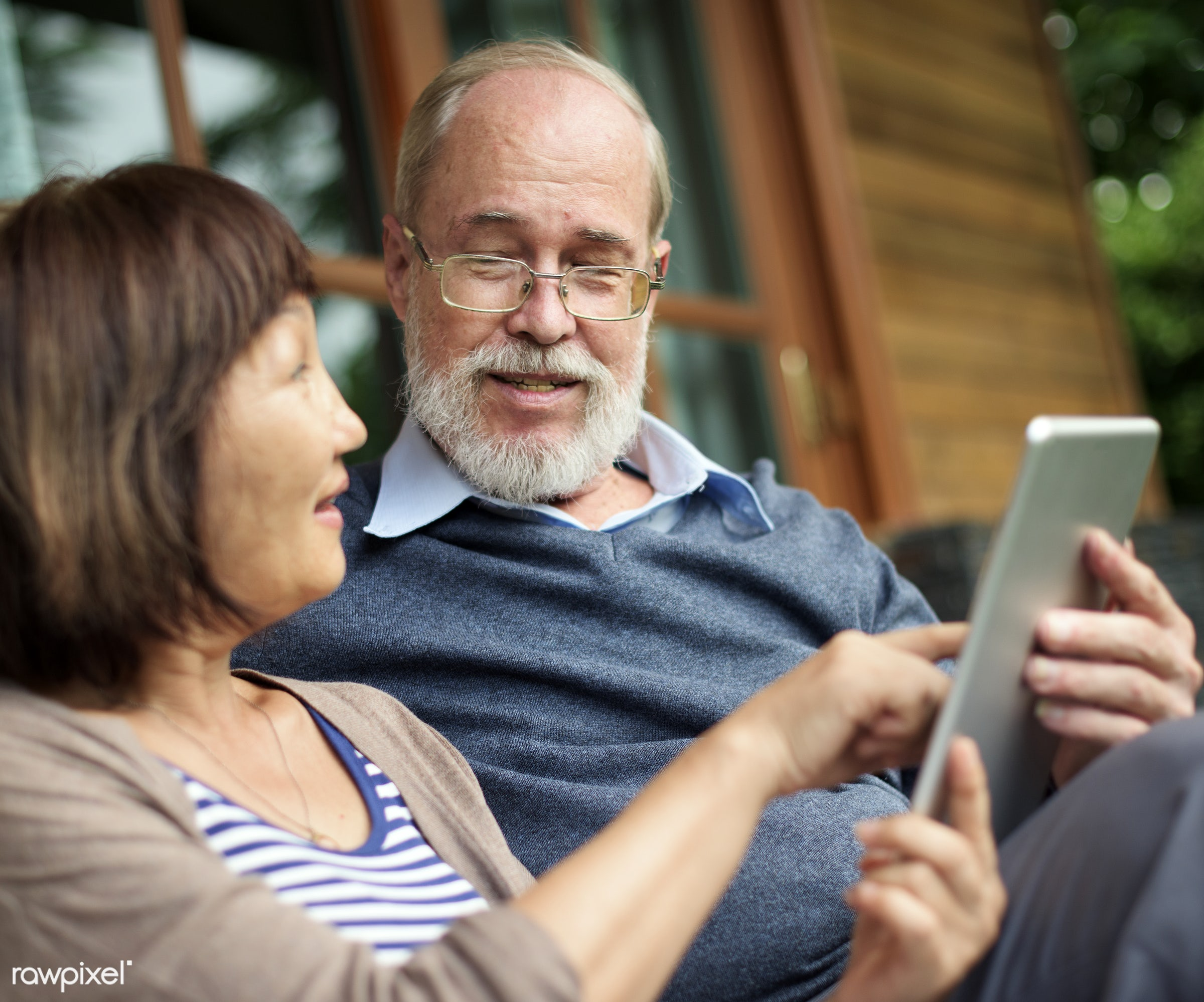 Senior couple sitting in front of a wooden cabin sharing a tablet - senior, asian, beard, browsing, care, cheerful, close,...