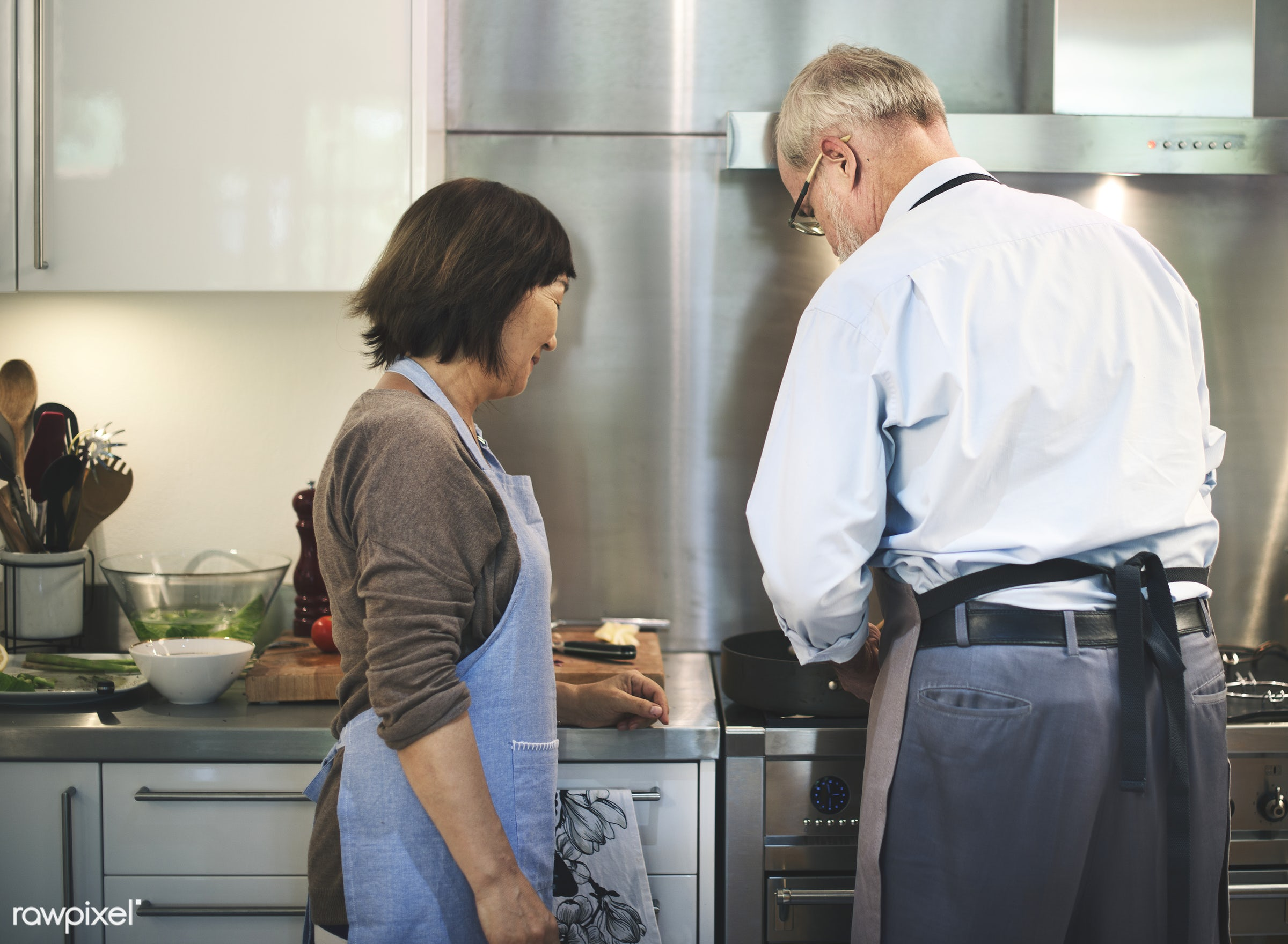Senior couple cooking together in the kitchen - couple, home, activity, apron, asian, breakfast, care, cheerful, chef, close...
