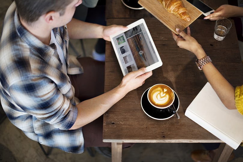 A man with a tablet at a coffee shop