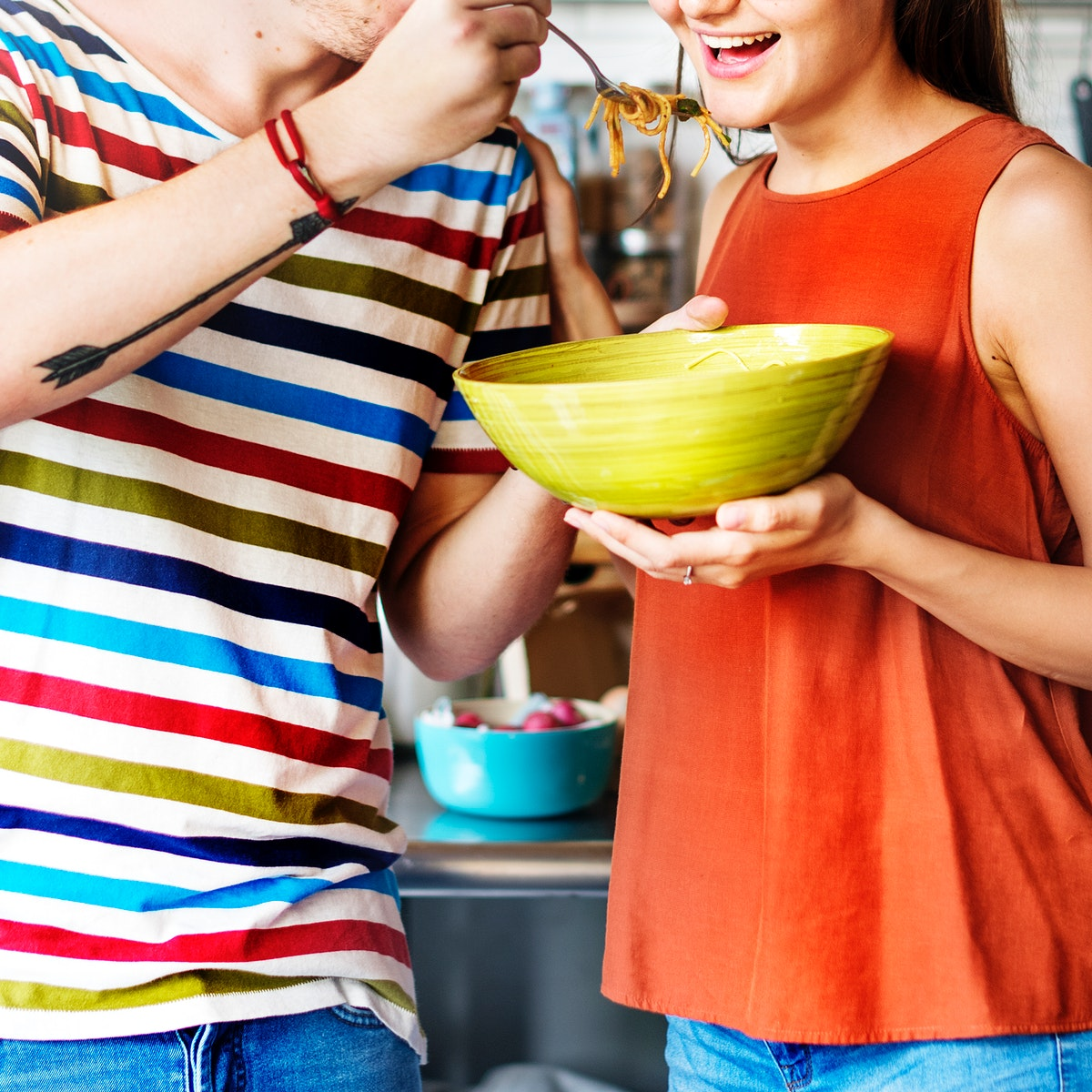 Couple sharing eating a bowl of spaghetti