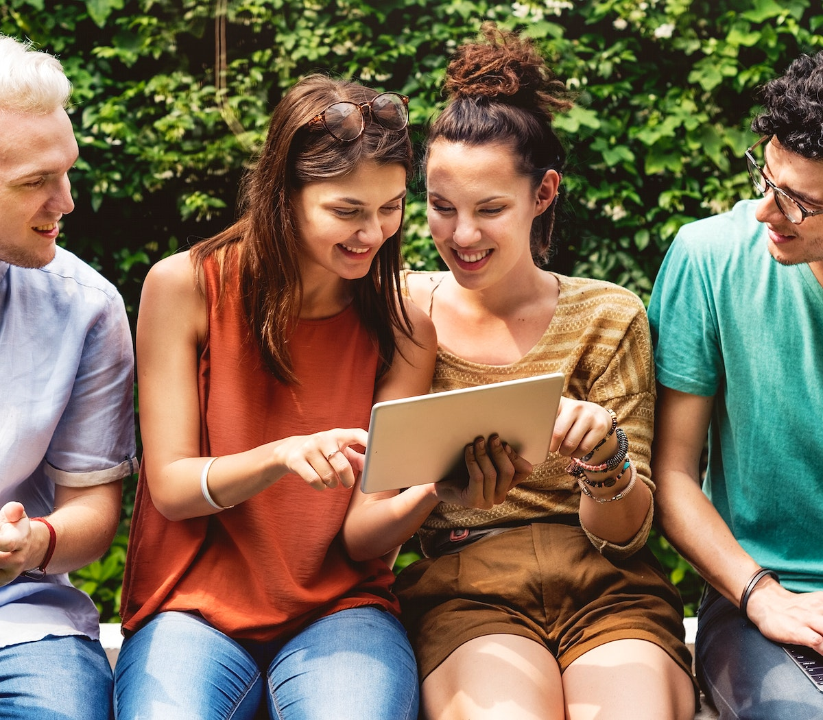 Group of diverse friends sitting using tablet together
