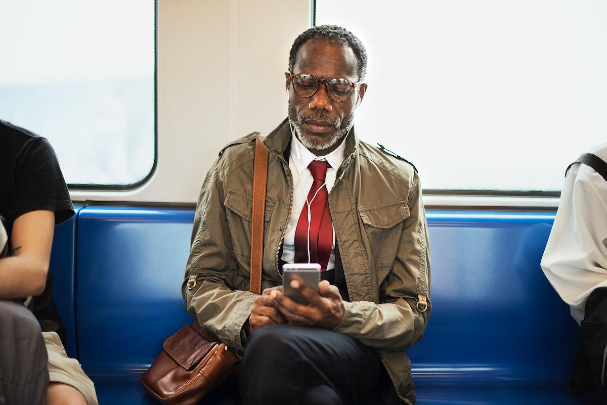African descent businessman is using earphones