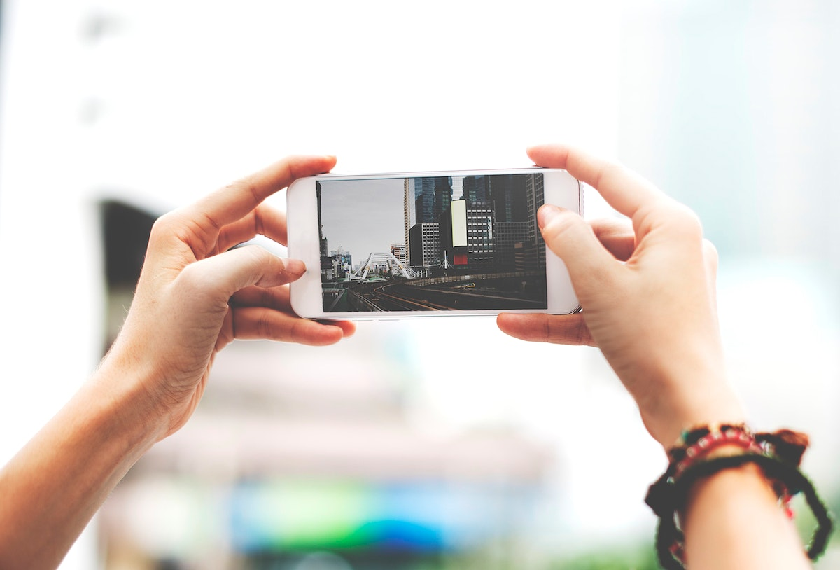 Hands holding mobile phone screen showing metro landscape city view photo