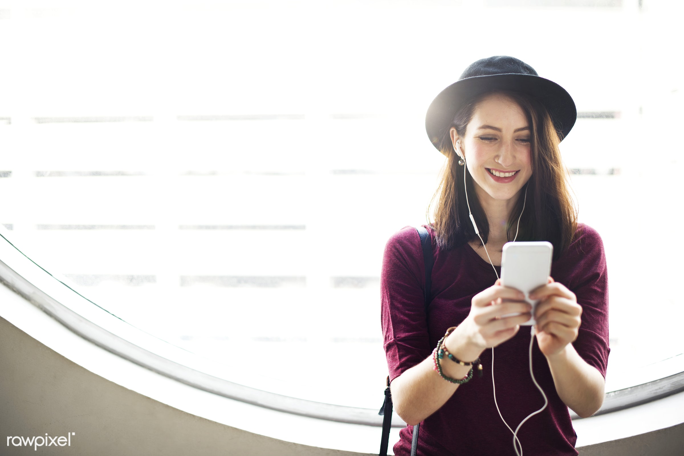 Young woman playing on her phone - podcast, thinking, activity, audio equipment, brown hair, calm, casual, cheerful,...