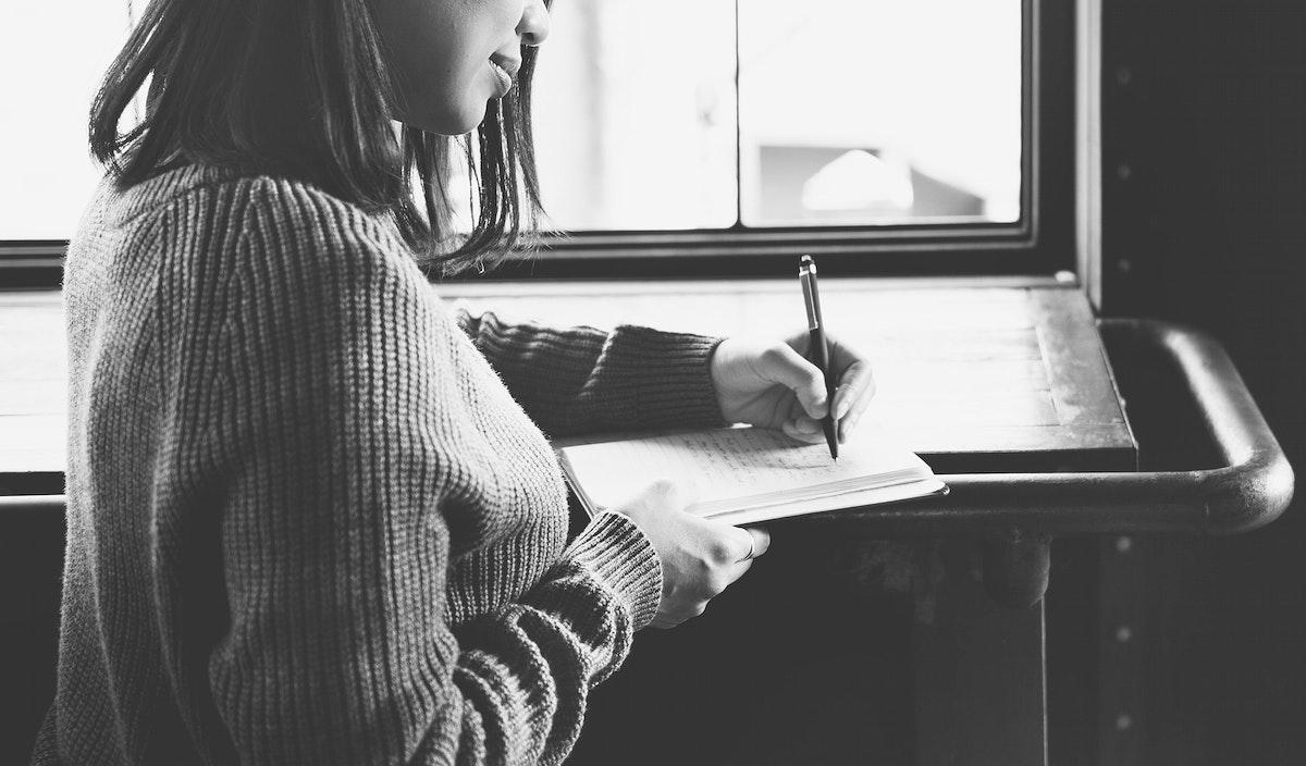 Closeup of asian woman writing notebook