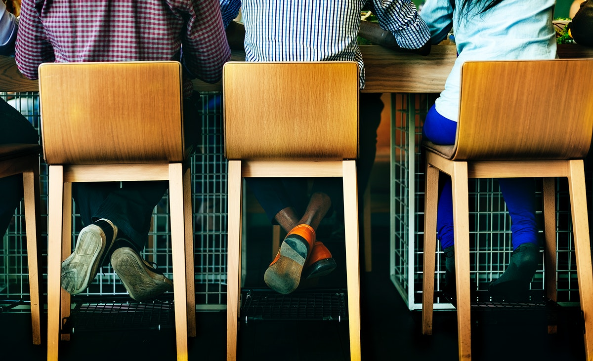 Rear view of diverse people sitting together at coffee cafe