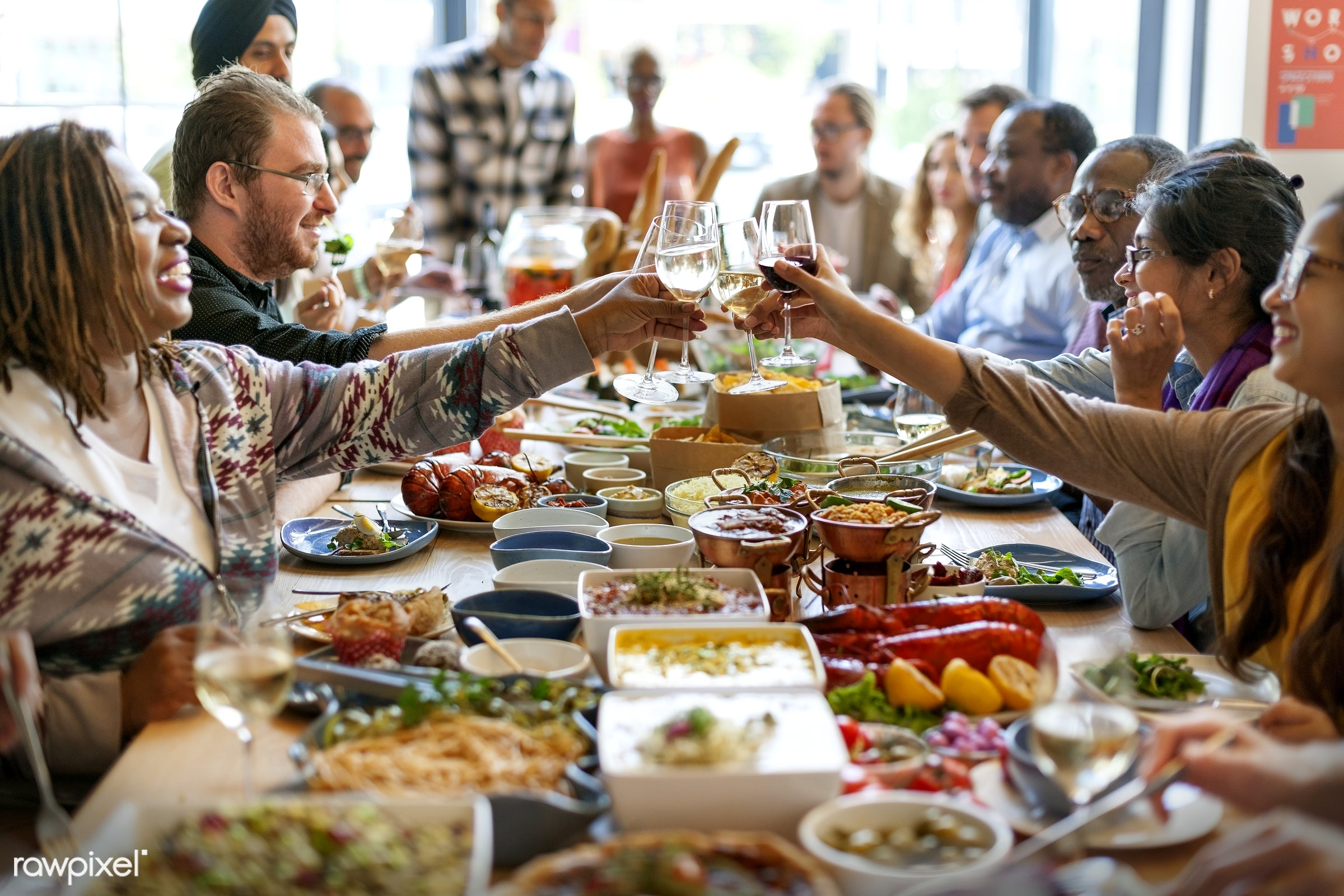 Group of diverse people are having lunch together - toast, african american, african descent, asian, black, cheerful, cheers...