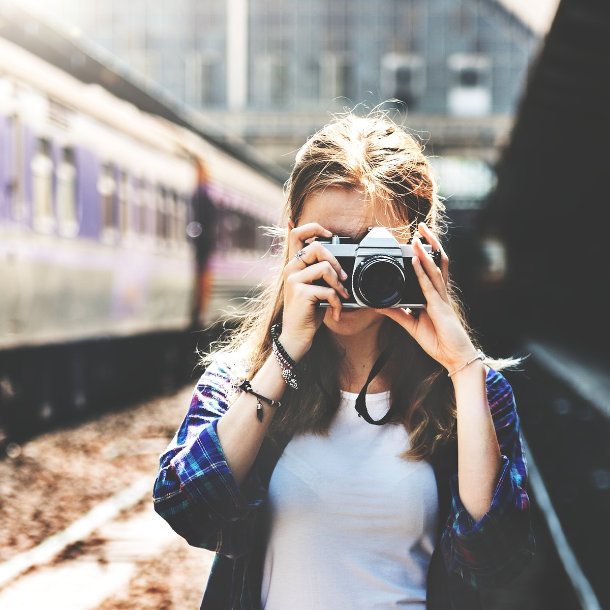 Young woman is taking photo with film camera