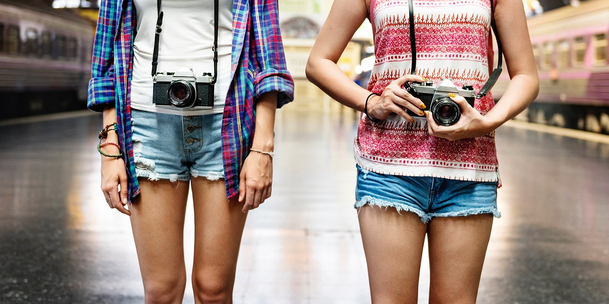 Two tourist women standing at train platform with camera