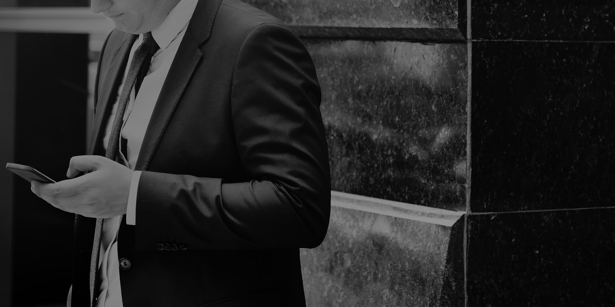 Closeup of businessman using mobile phone gray scale