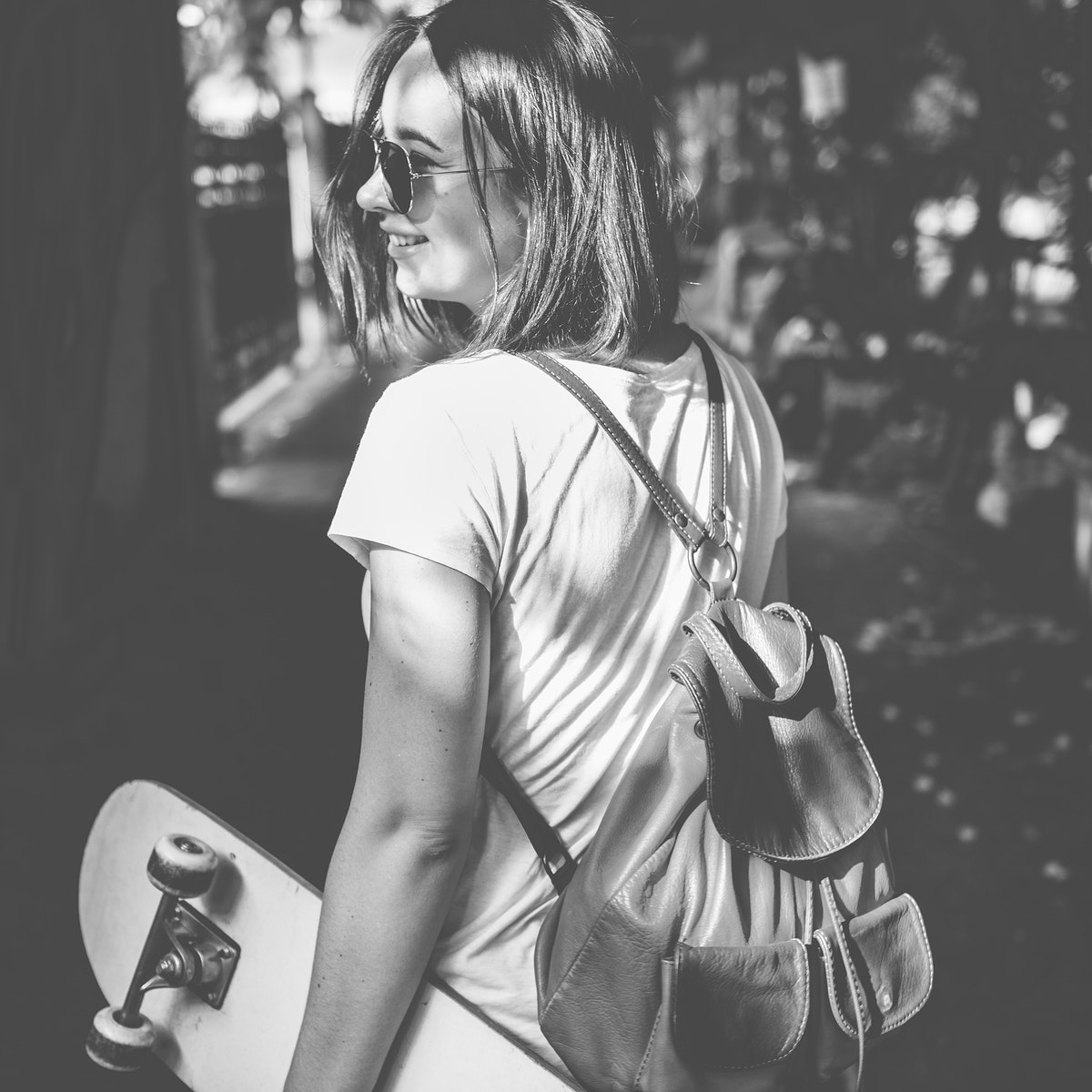 Woman holding skateboard outdoors grayscale