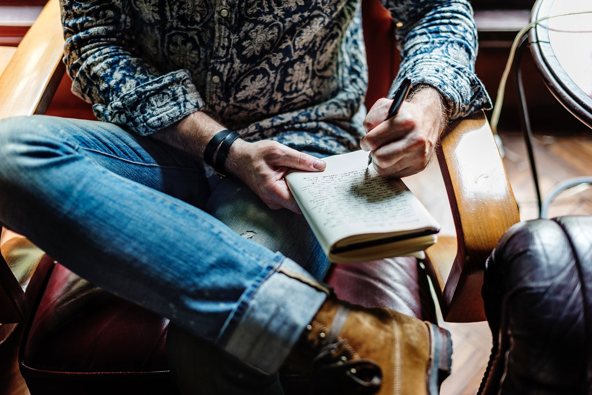 Closeup of journalist man sitting writing notebook