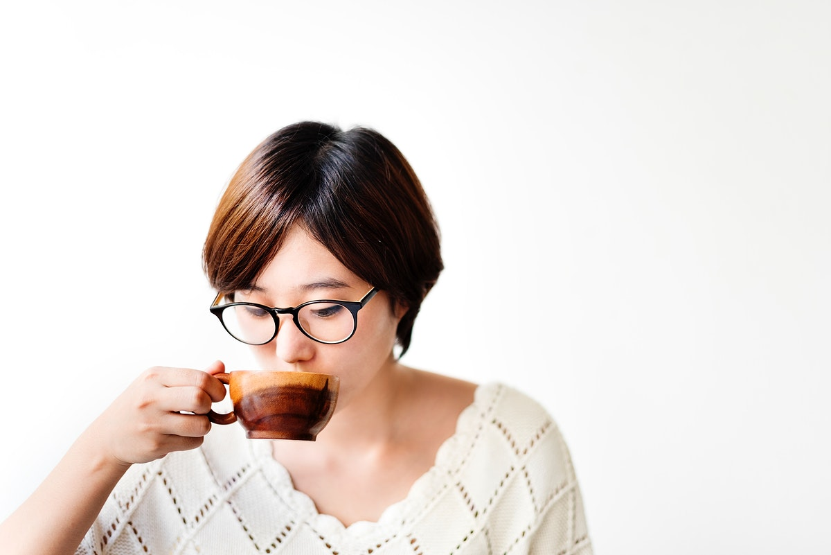 Asian woman drinking coffee with wooden cup