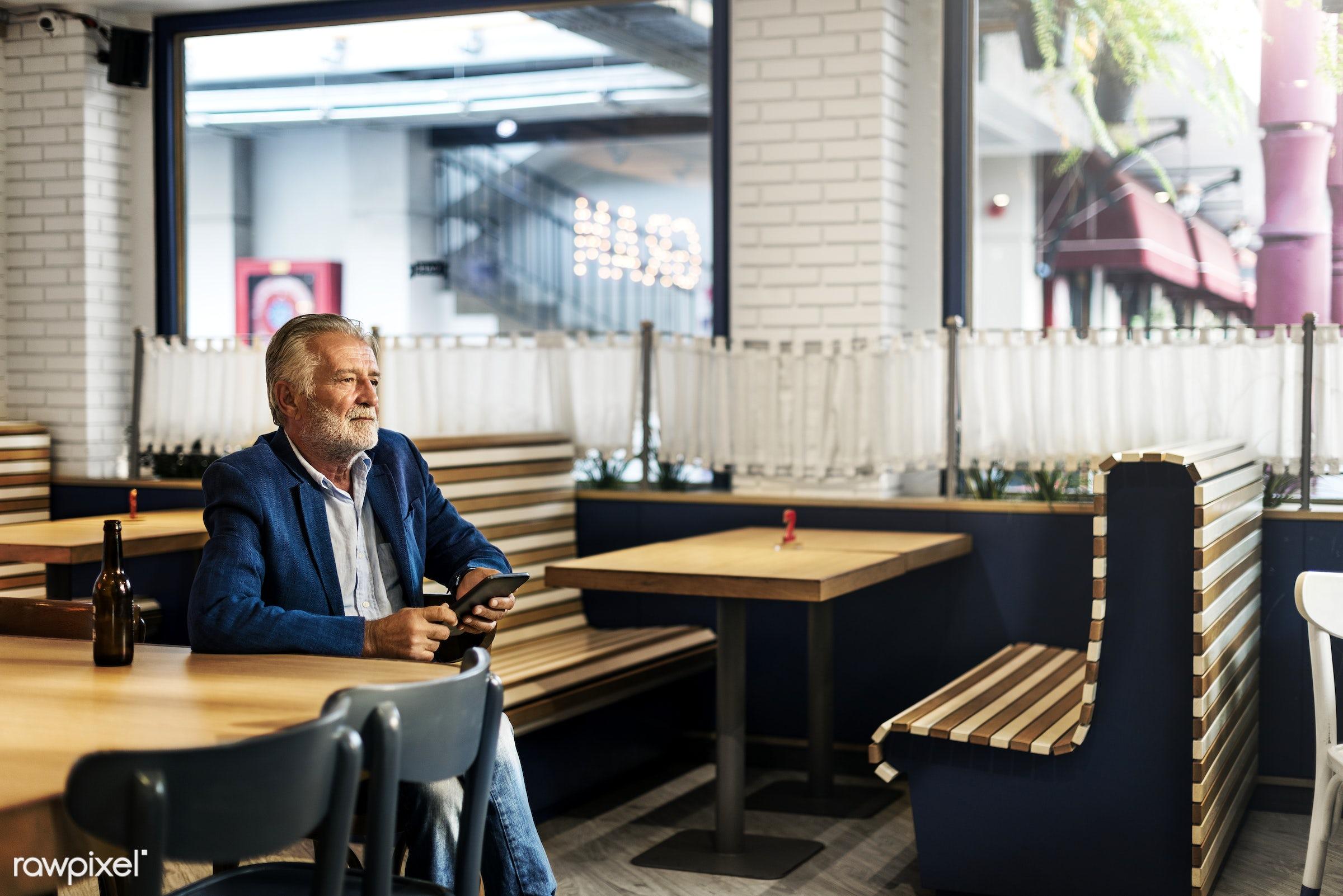 Elderly man is sitting in a pub - alone, bar, beard, beer, beverage, casual, depressed, device, digital, drink, elderly,...