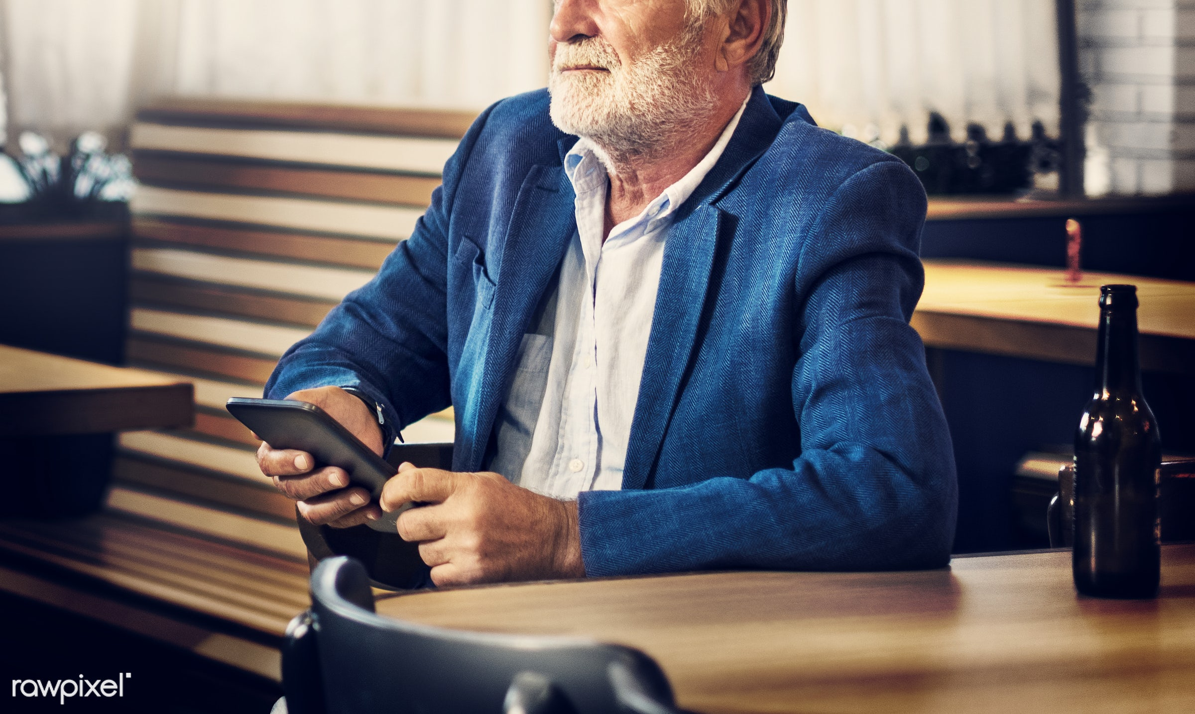 Elderly man is sitting in a pub - beer, alone, bar, beard, casual, communication, connection, device, digital, elderly,...
