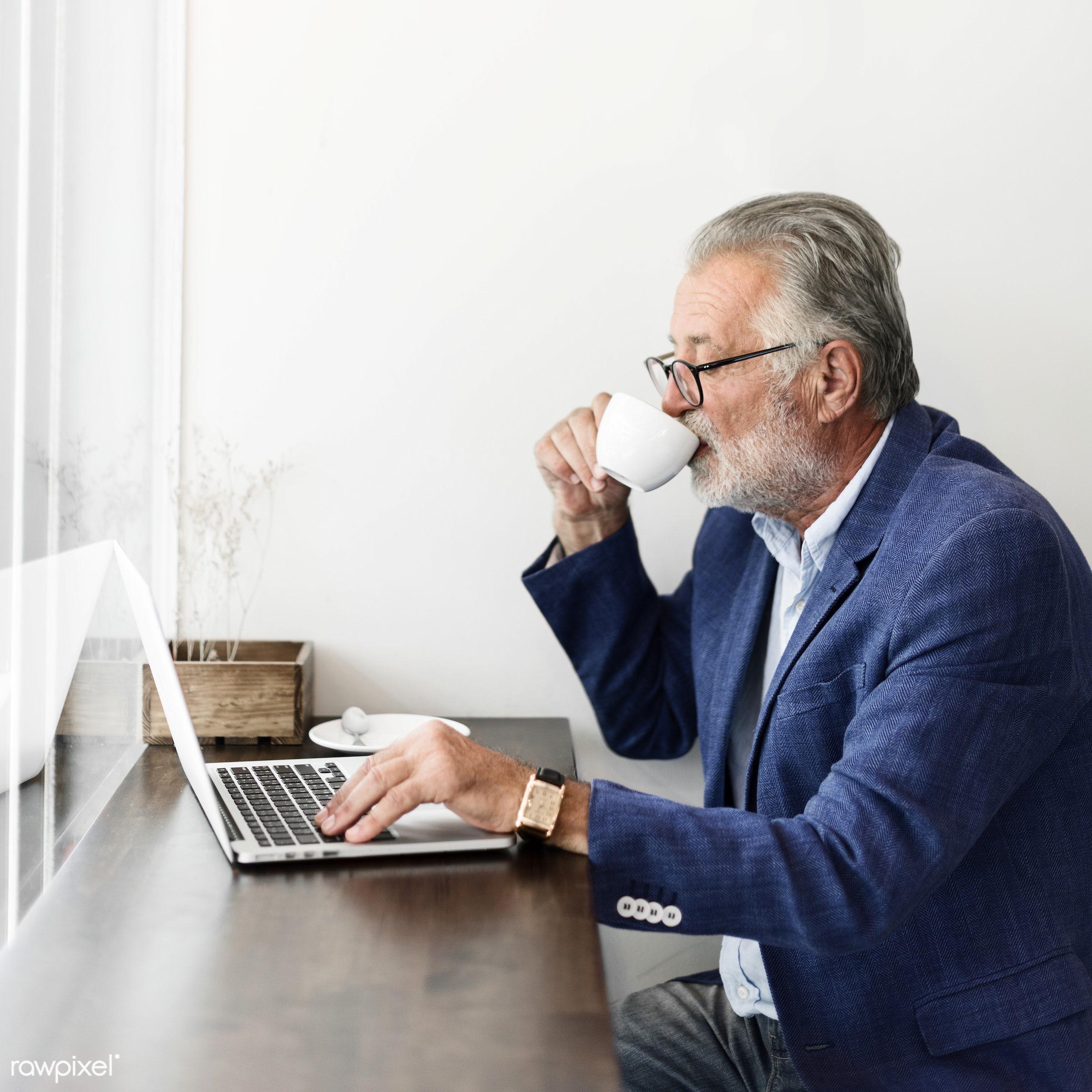 Elderly man is using computer laptop - elderly, digital, shop, alone, casual, coffee shop, communication, computer,...