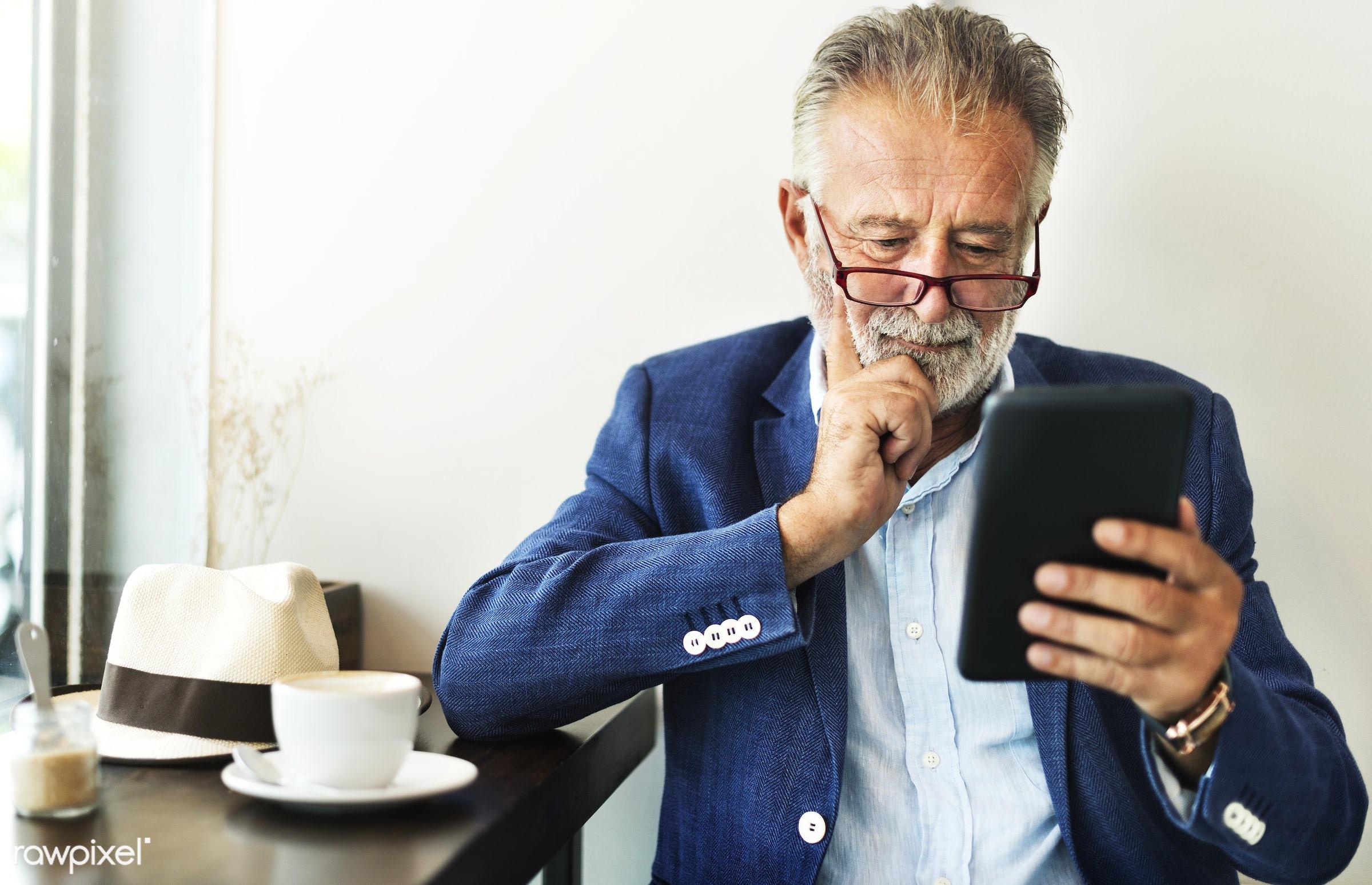Elderly man is using digital tablet - elderly, alone, beard, casual, communication, connection, device, digital, hipster,...