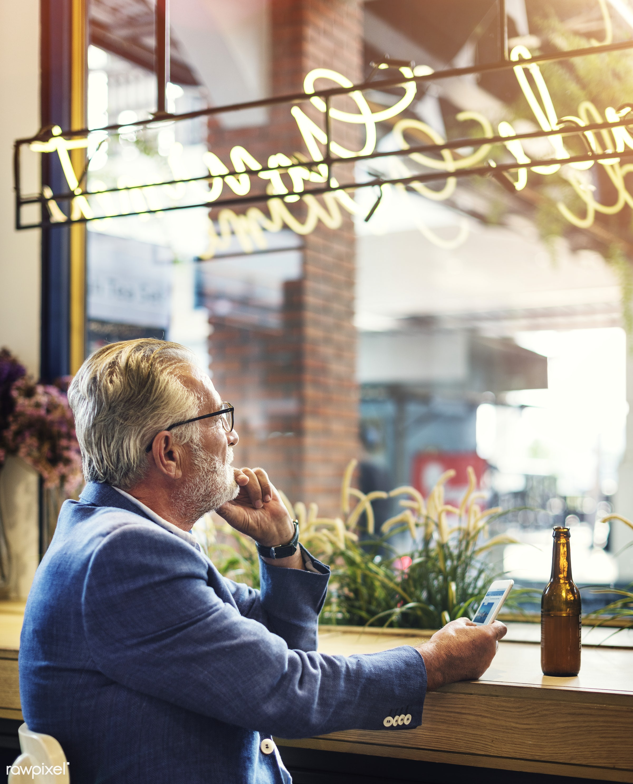 Elderly man is sitting in a pub - beer, alone, bar, beard, beverage, casual, caucasian, cellphone, depressed, device,...