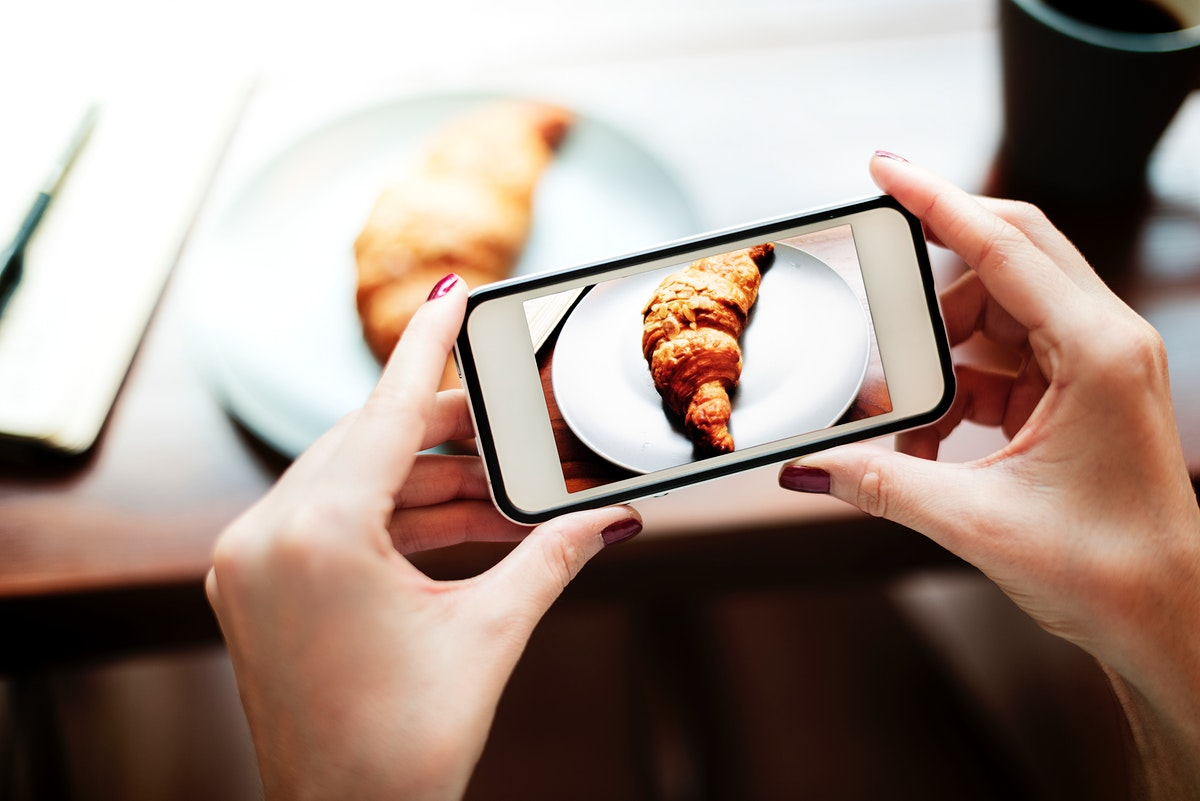 Closeup of hands holding mobile phone taking croissant photo