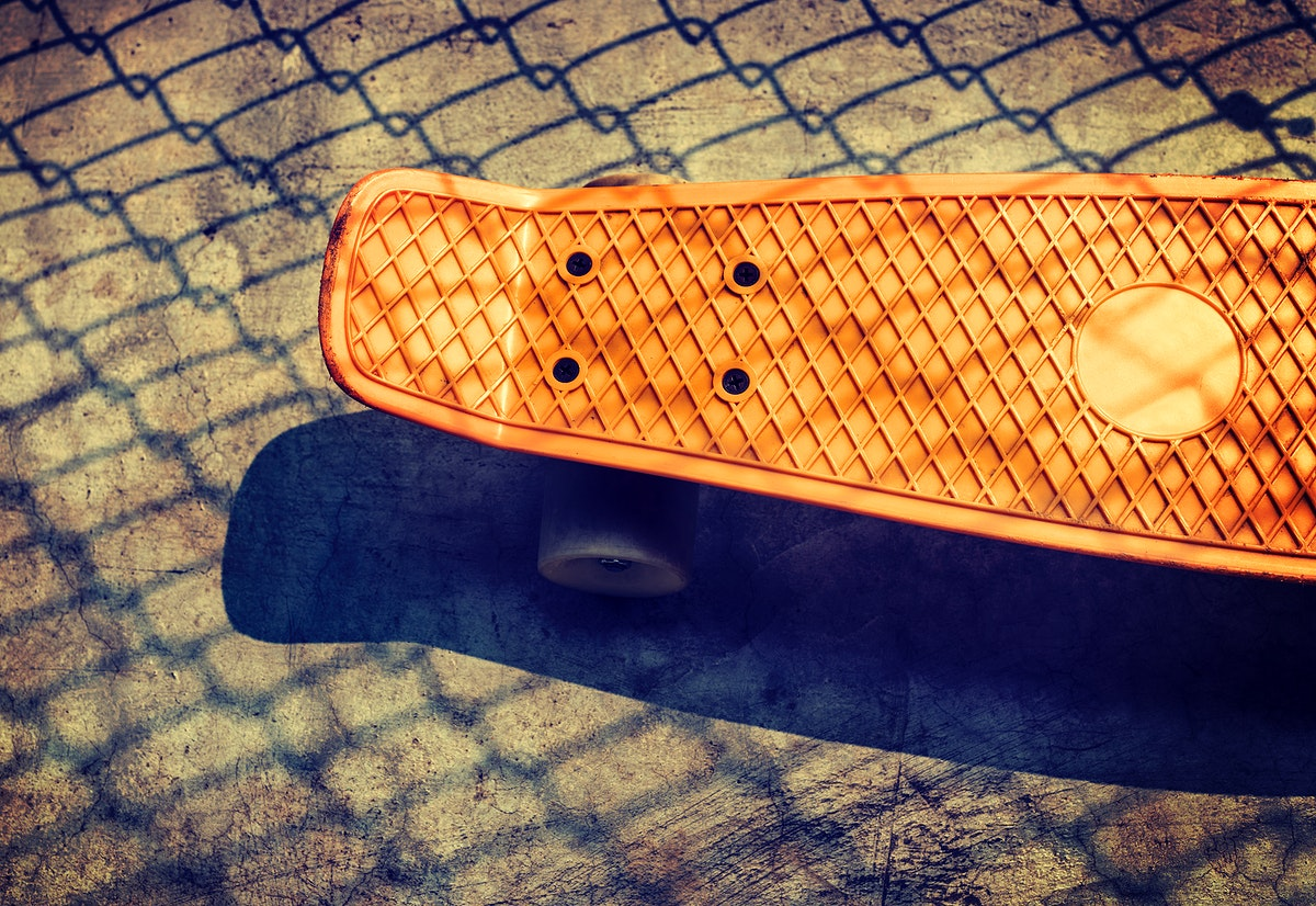 Aerial view of orange skateboard on the ground