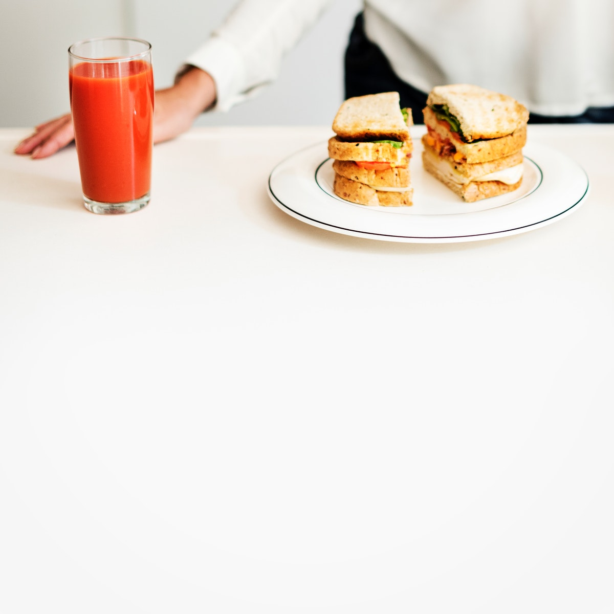 Closeup of sandwich and juice on white table
