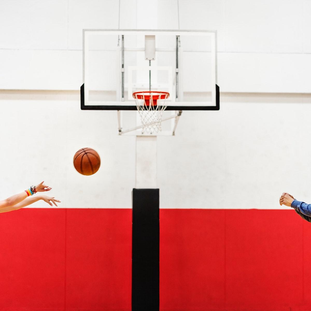 Hands shooting basketball to the net hoop