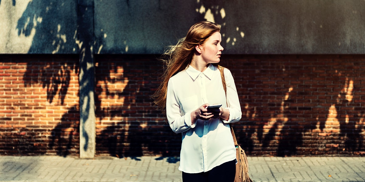 Young caucasian woman standing using mobile phone outdoors