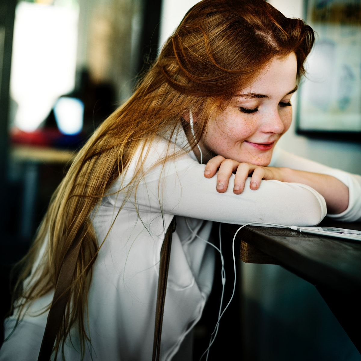 Young caucasian woman sitting listening to music