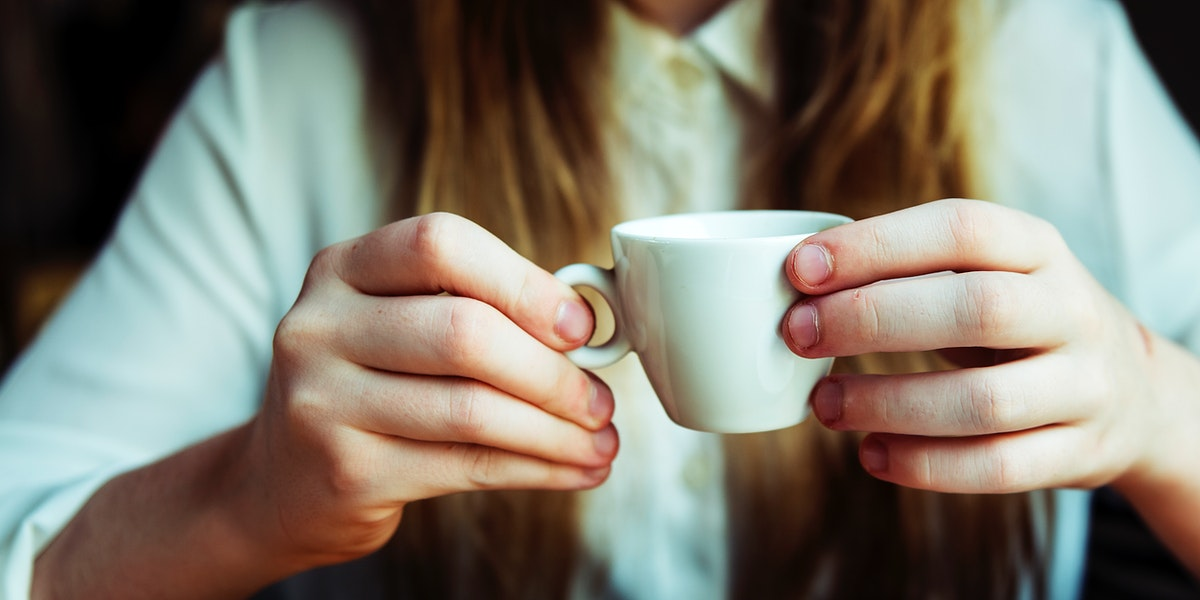 Closup of woman hands holding coffee cup