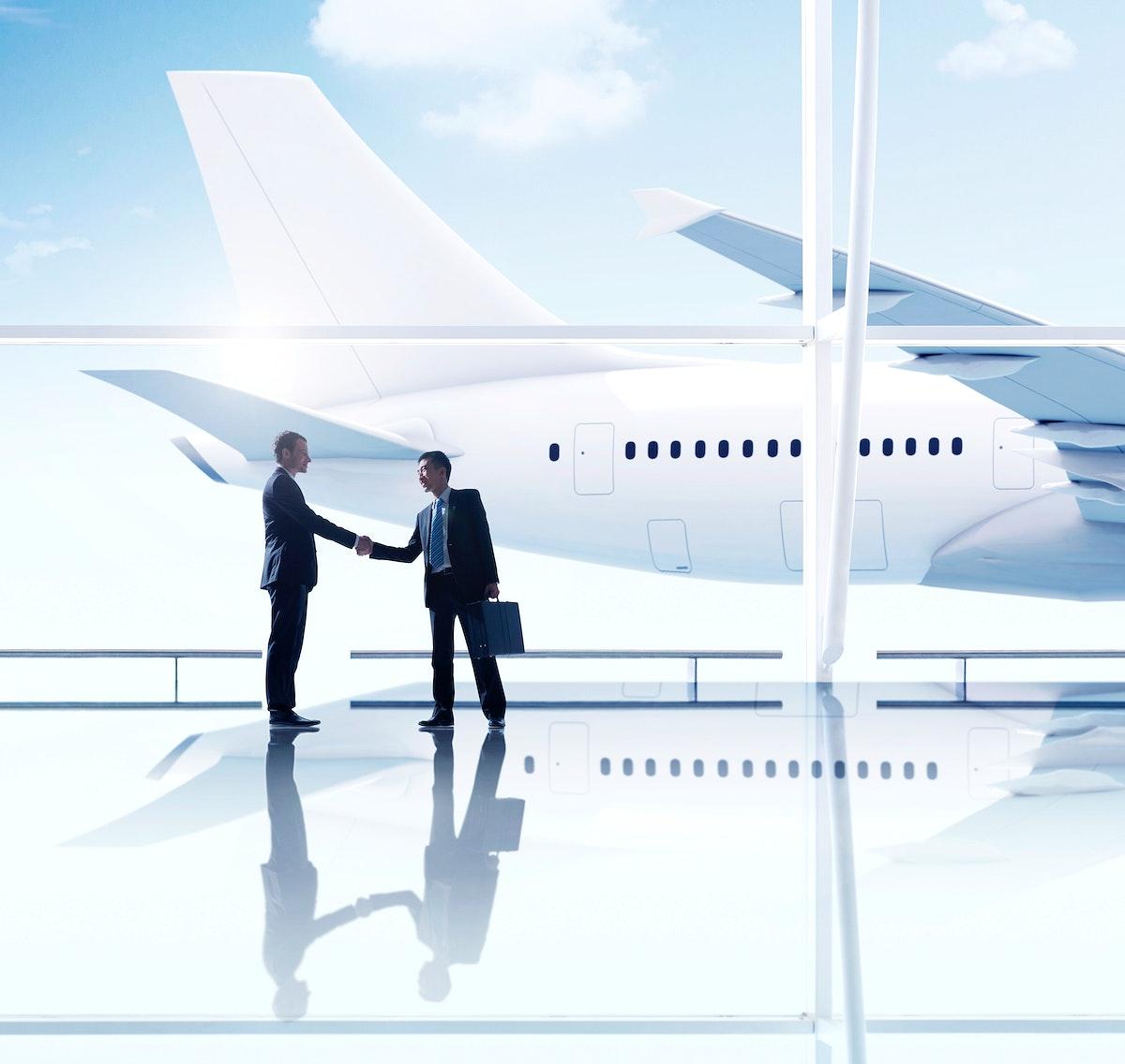 Western and asian businessmen handshake airport meeting
